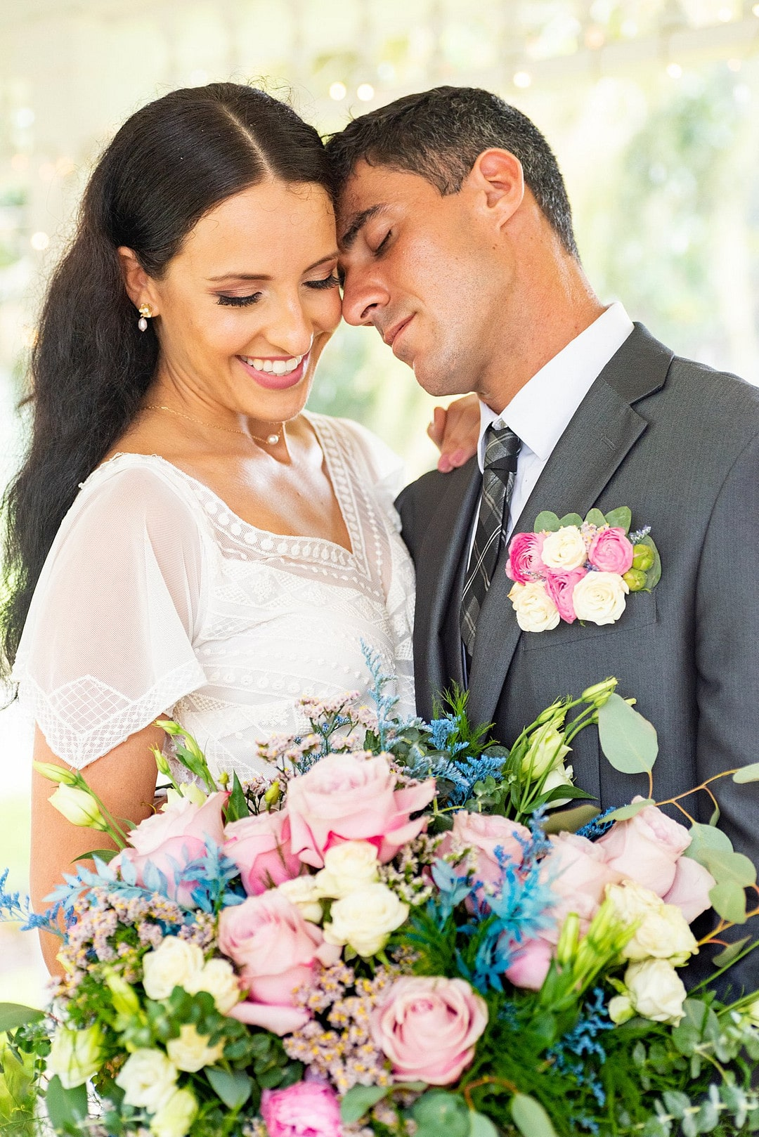 close up of bride and groom touching faces and bride smiling while holding bouquet towards bottom of image and grooms pocket boutonniere