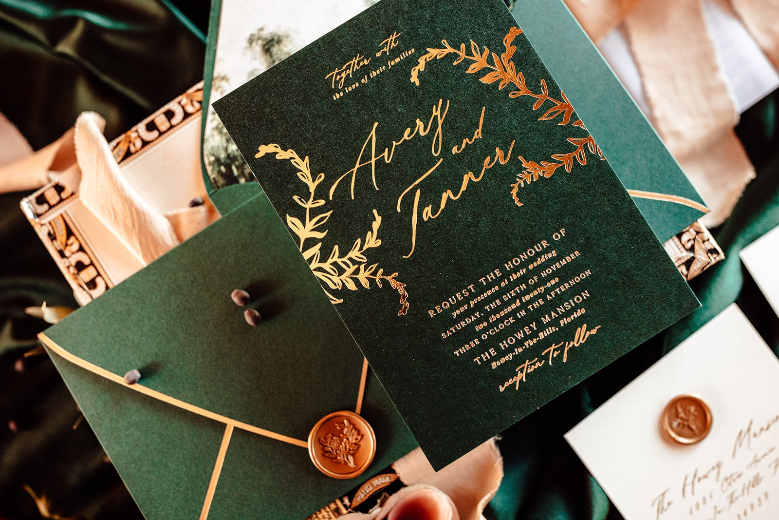 close up shot of emerald green and gold wedding invitation with envelope with gold wax seal next to it
