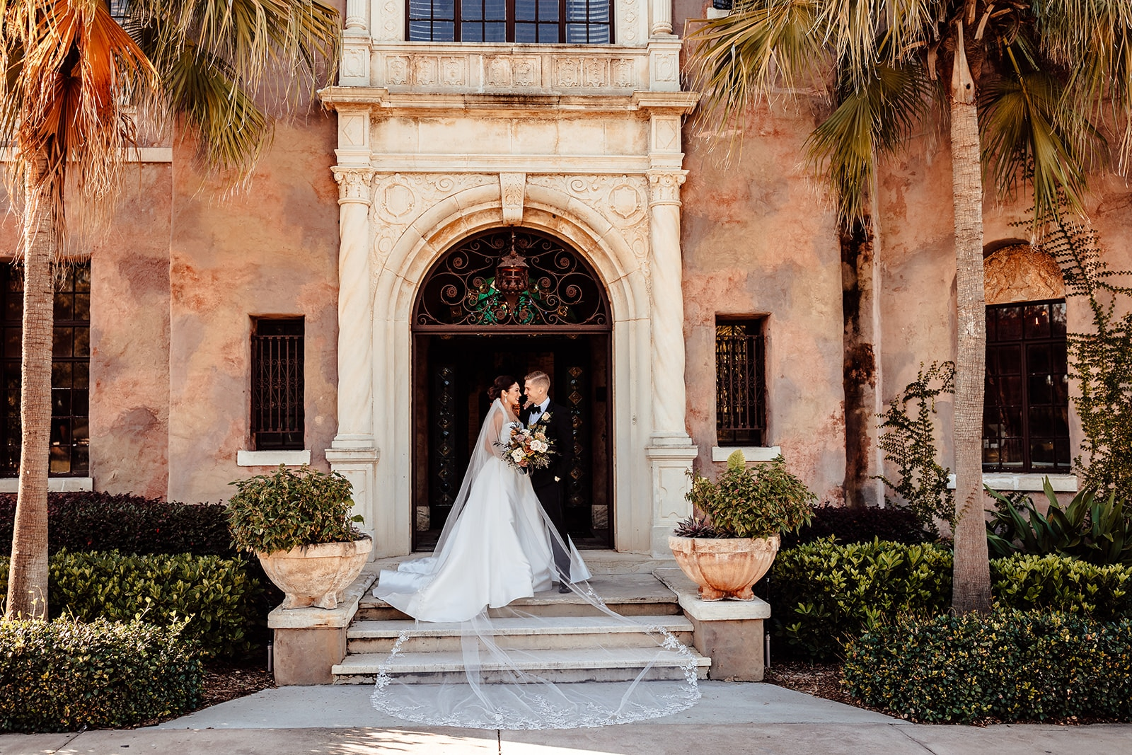 far away shot of bride and groom looking at each other on the front porch of historic mansion with wrought iron door and frame