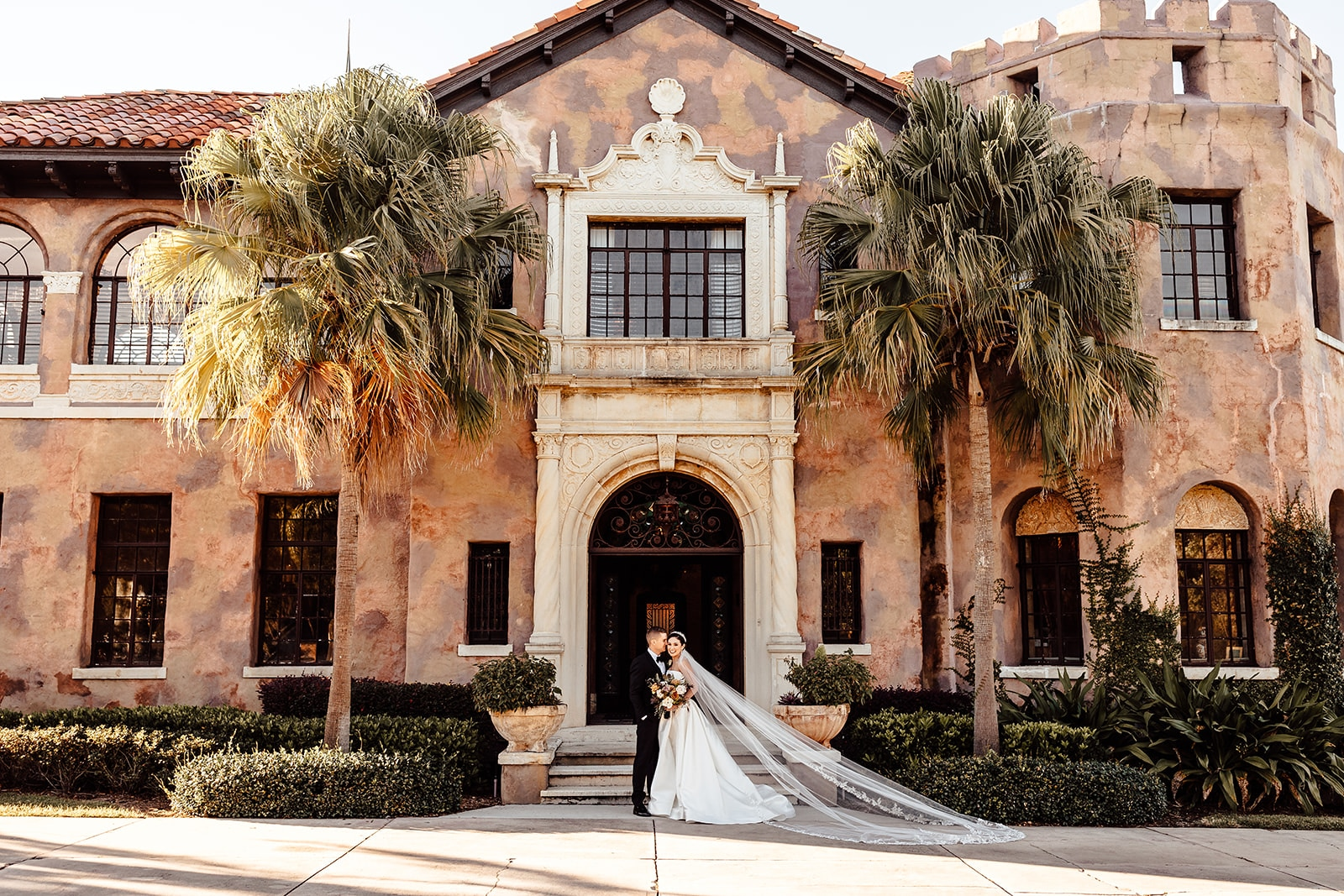 historic mansion with amazing architecture with two palm trees on either side of the front door with newlyweds in front center of the image