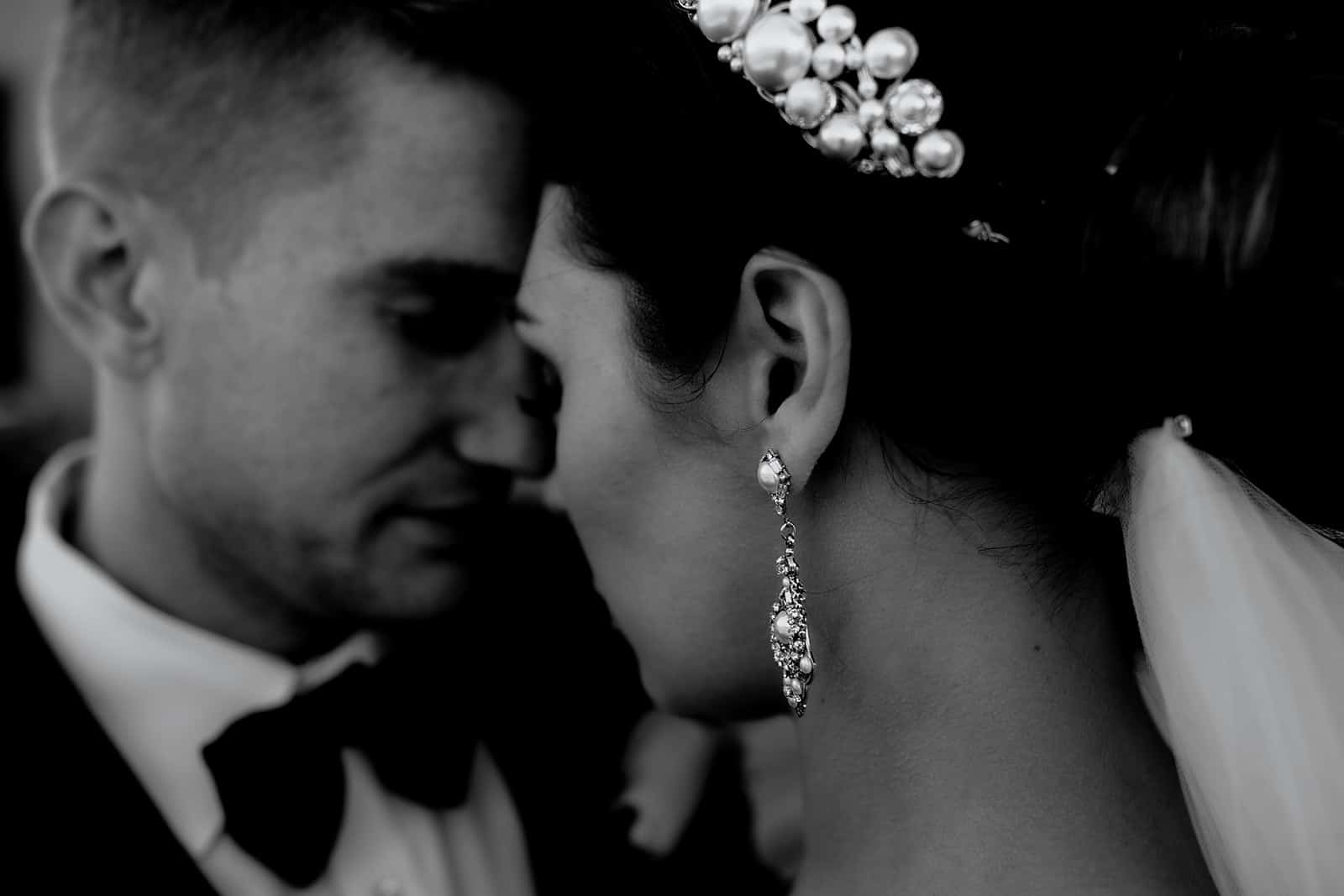 black and white close up looking over brides shoulder as the bride and groom touch foreheads and dangling earring in the center of the image