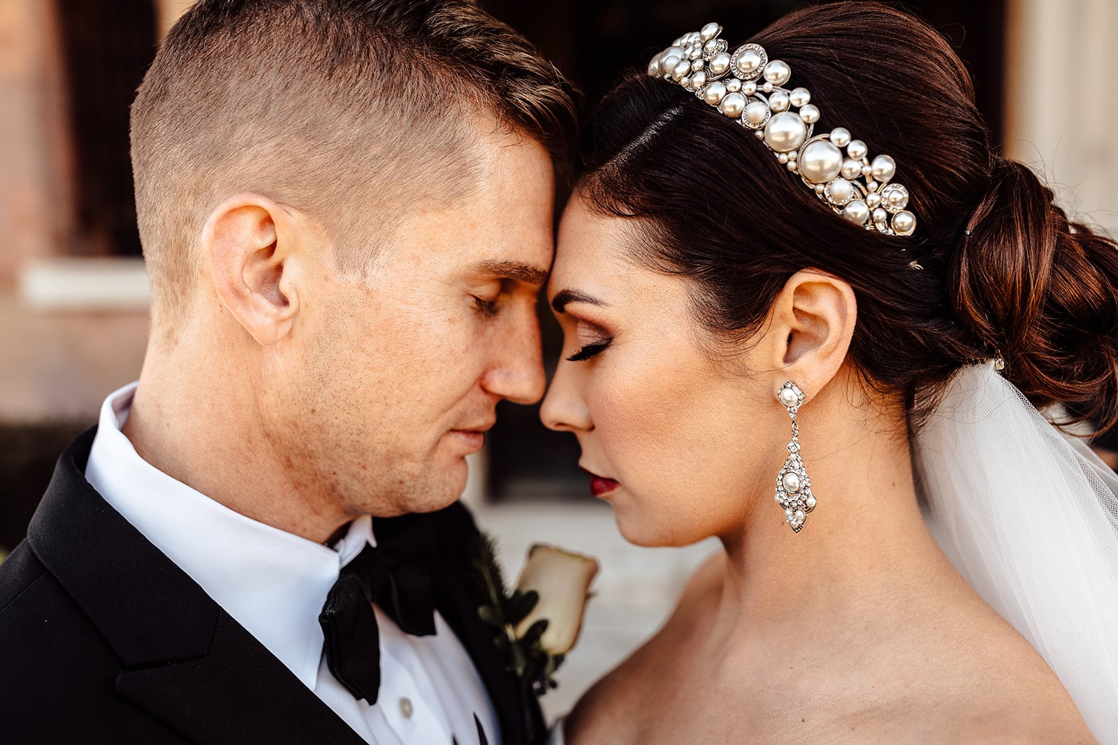 close up of bride and groom touching foreheads together with eyes closed and brides pearl and silver crown hair piece with dangling silver earring