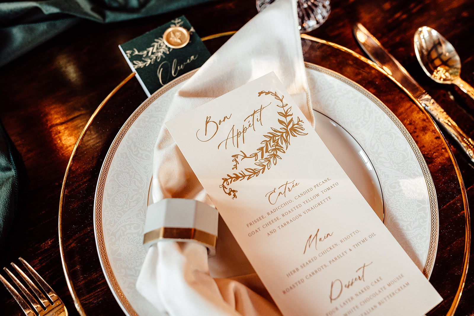 close up of gold and white dinner plate with gold flatware around is with napkin in ring on the edge of the plate and hand designed dinner menu on top
