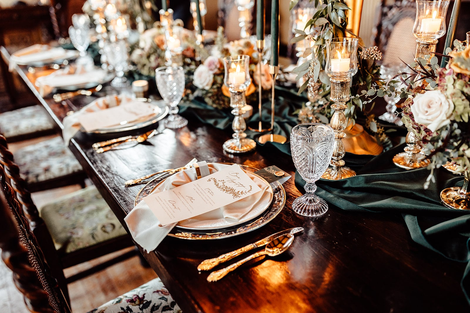 wooden table set for wedding reception design with votive candles and emerald green linen spread on the table and greenery mixed with flowers and two big candelabras