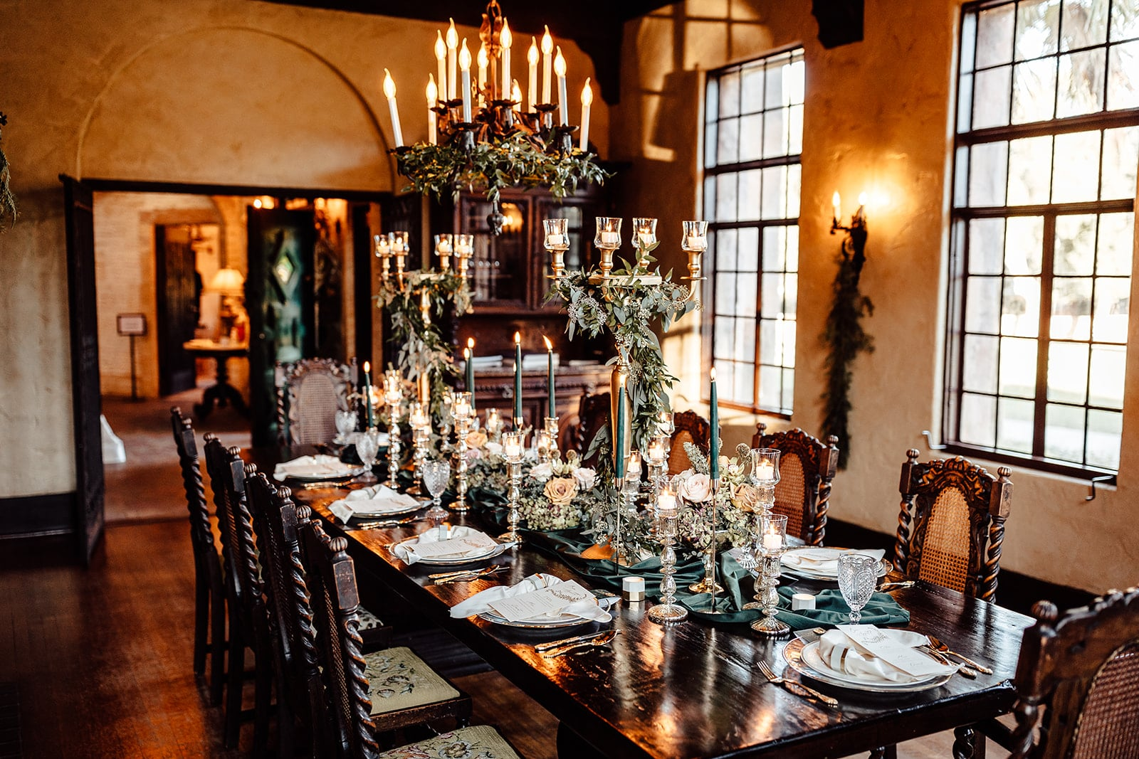 historic room with old wooden table complete with place settings for wedding reception and table with elegant emerald gold wedding decor including candelabras with garland and other accents of the colors