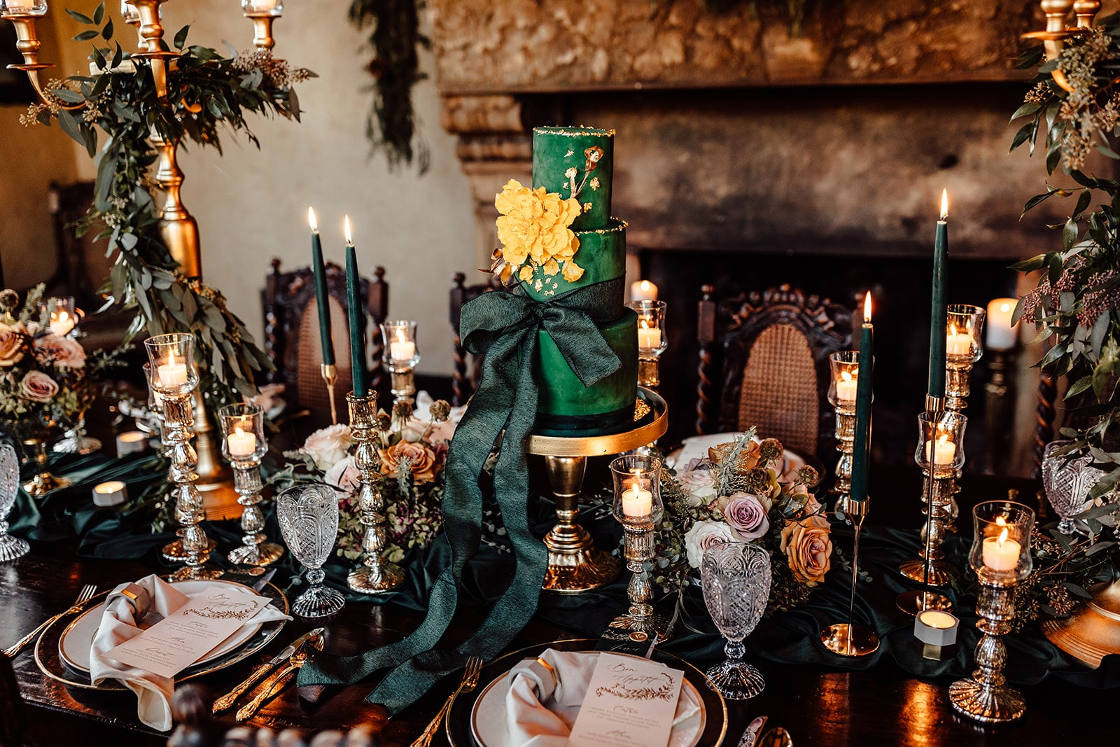 emerald green cake in the middle of wedding decorated table with elegant emerald green and gold decor cake with giant emerald green bow on the bottom tier