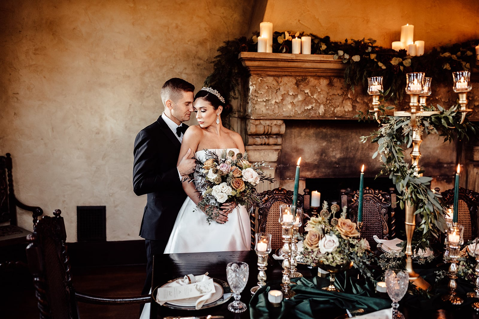 bride and groom stand together next to fire place decorated with garland and candles with table in front of them decorated with floral arrangements and a huge candelabra with garland attached as well as other candles on the table and flatware with plates