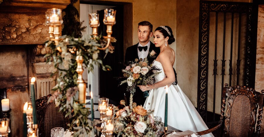 couple on wedding day stand close to each other looking off in the distance to the left in front of decorated table with candelabra and greenery