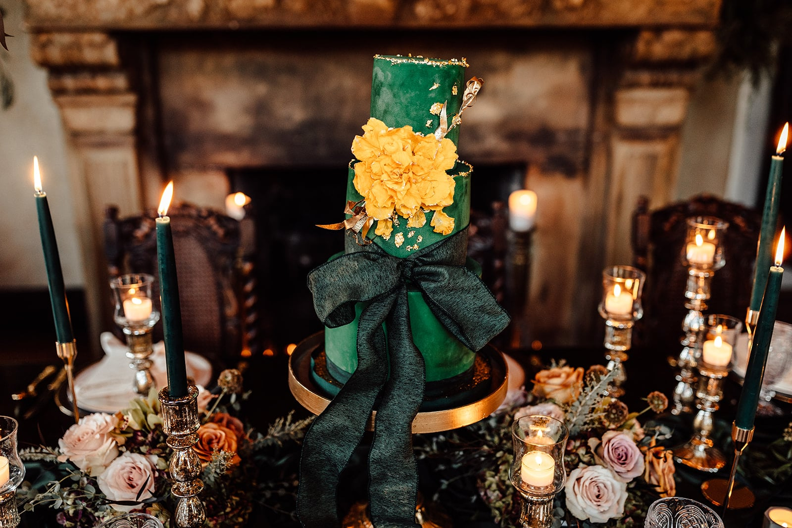 emerald green colored three tier wedding cake with big golden yellow flower on side and giant emerald green bow on the bottom tier on decorated tabletop