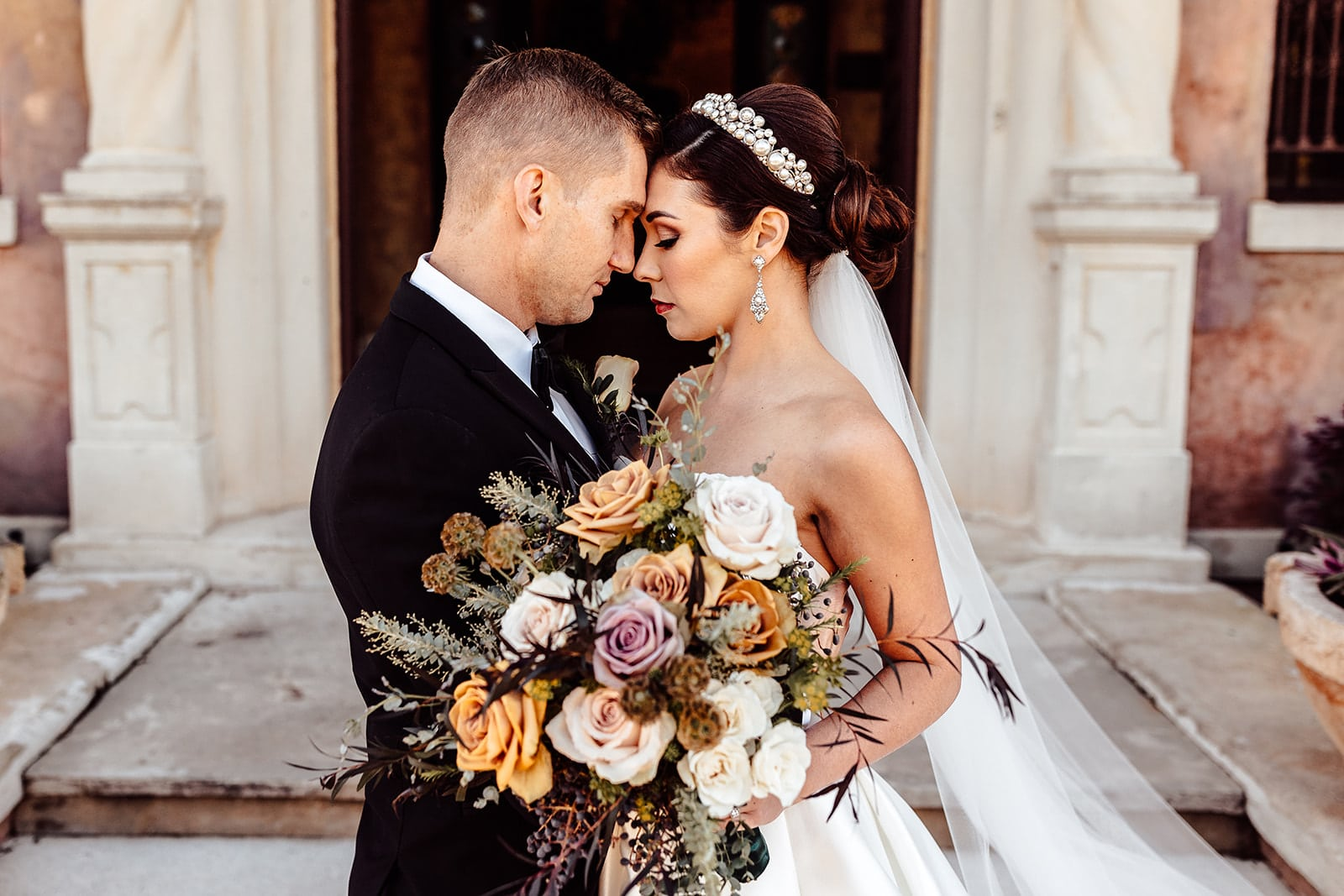 wedding portrait of bride and groom touching forheads and noses while bride holds bouquet in front of them