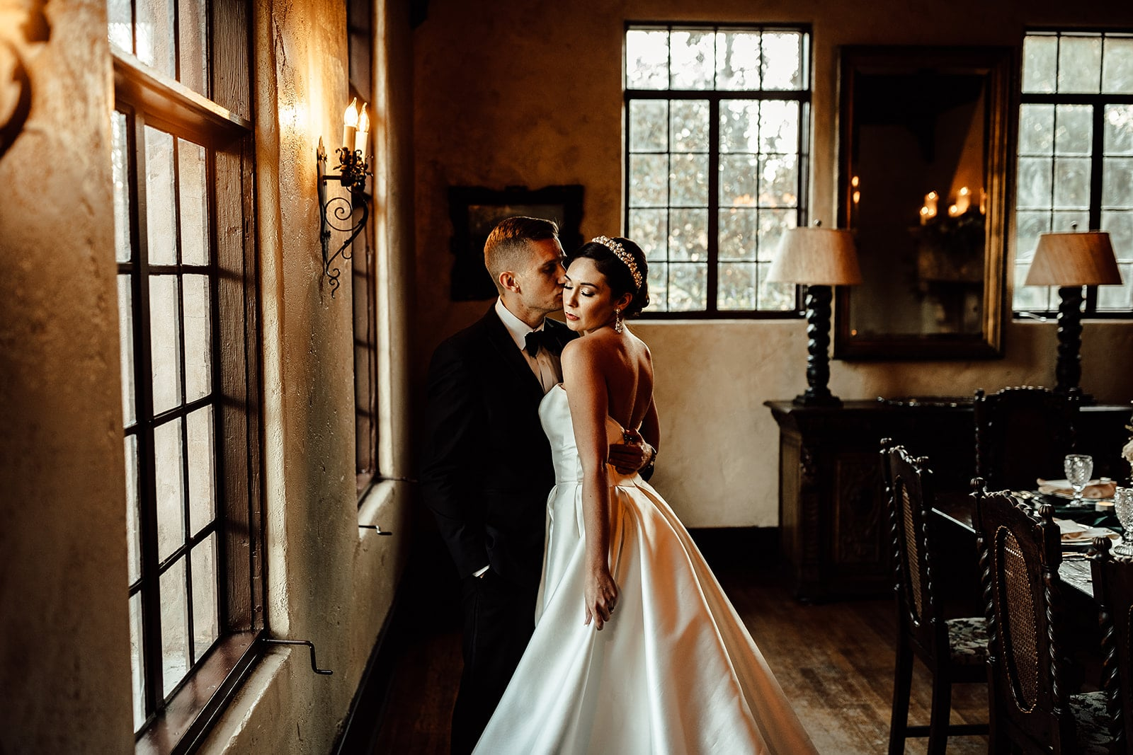 couple on wedding day in historic looking room next to window as groom kisses brides cheek and she looks down at the floor