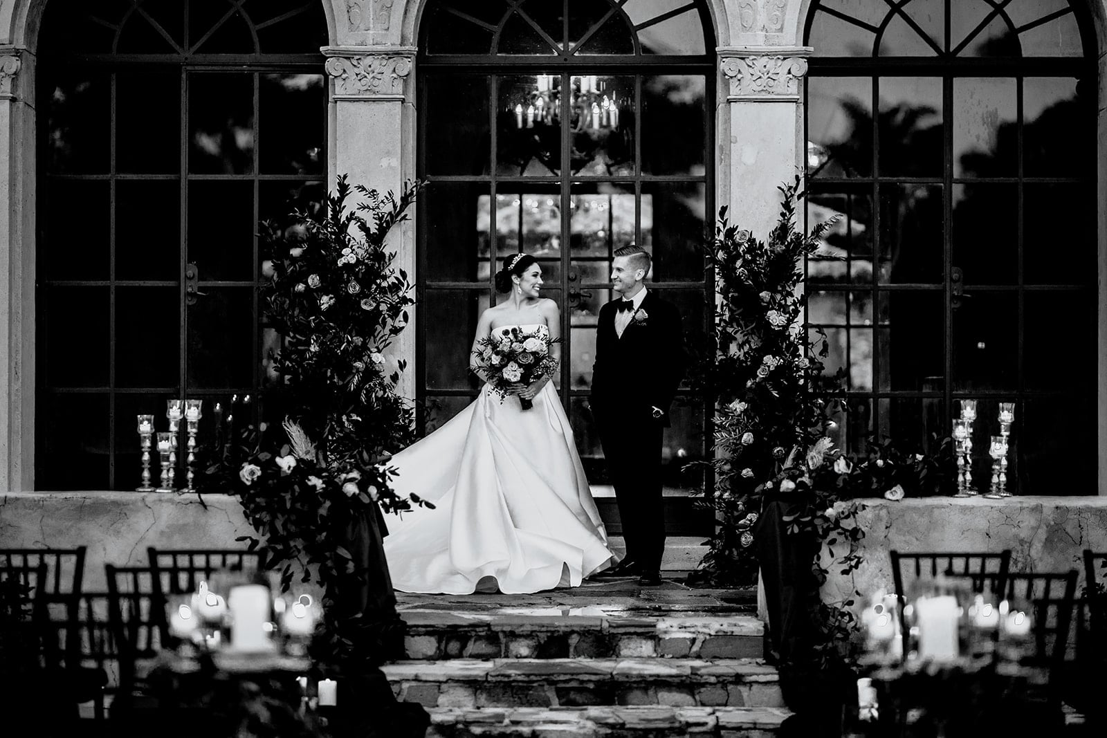 black and white image of couple in wedding day attire looking at each other standing facing the camera in their ceremony space decorated with floral arrangements
