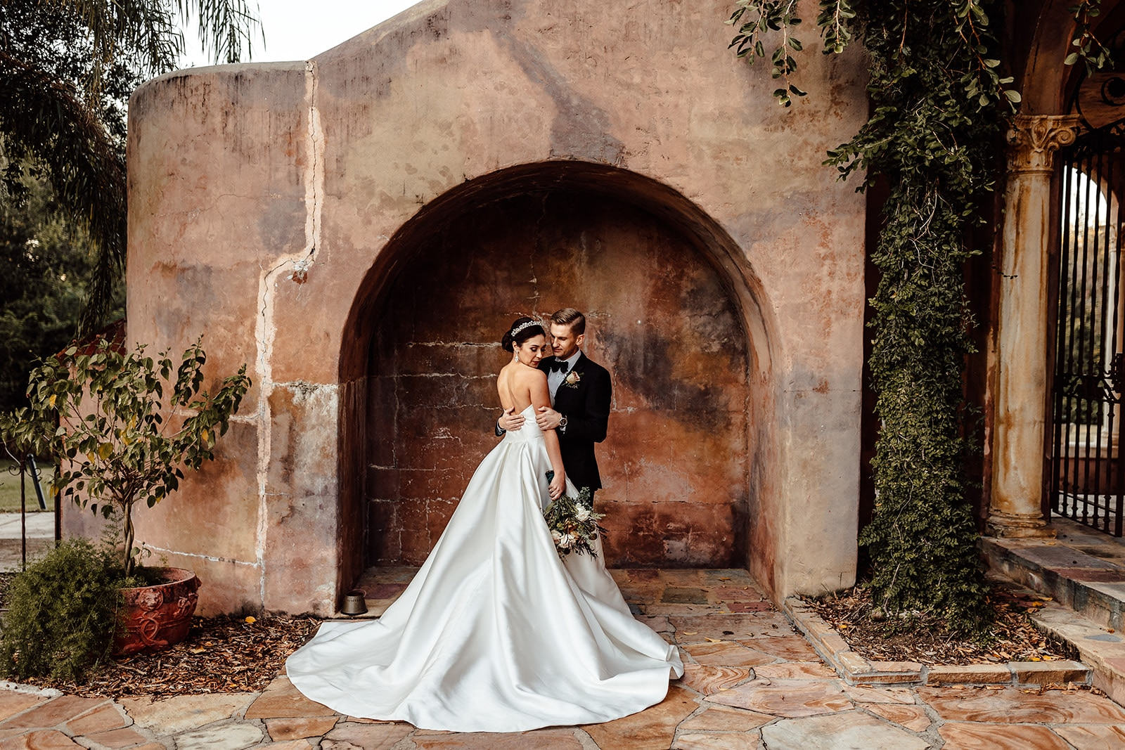 couple stand together in front of unique alcove outside close to each other with brides elegant ballgown