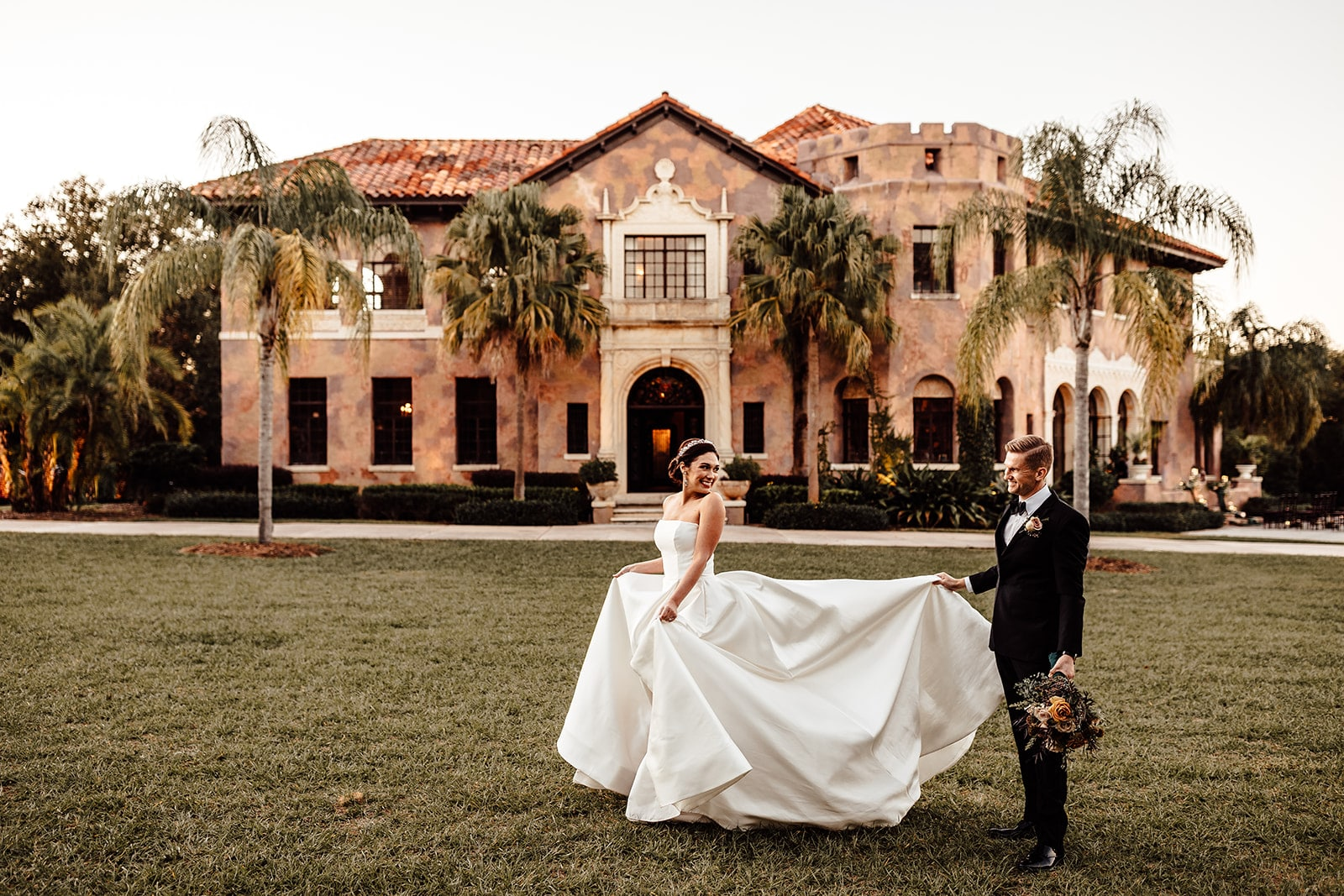 bride walks in grass looking back at groom holding her bridal gown up and bouquet in the other hand with the big historic mansion in the background