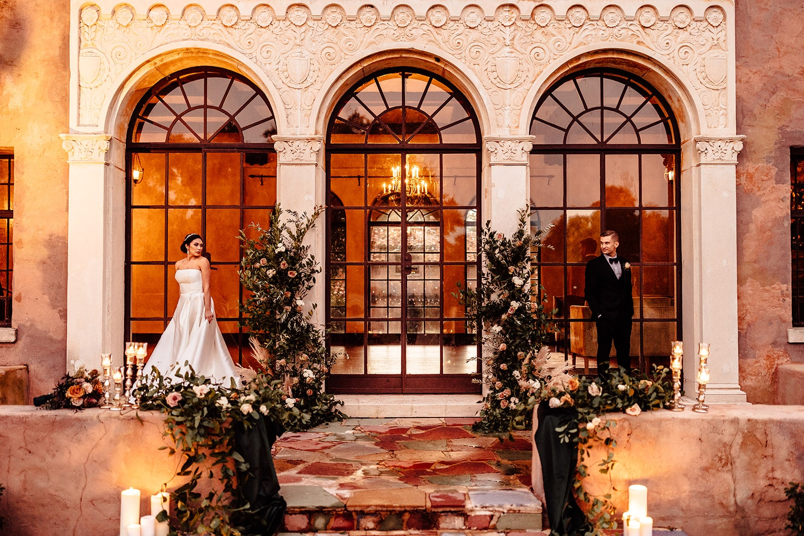 decorated columns in between large windows of greenery as bride and groom stand on opposite sides of the decor looking at each other