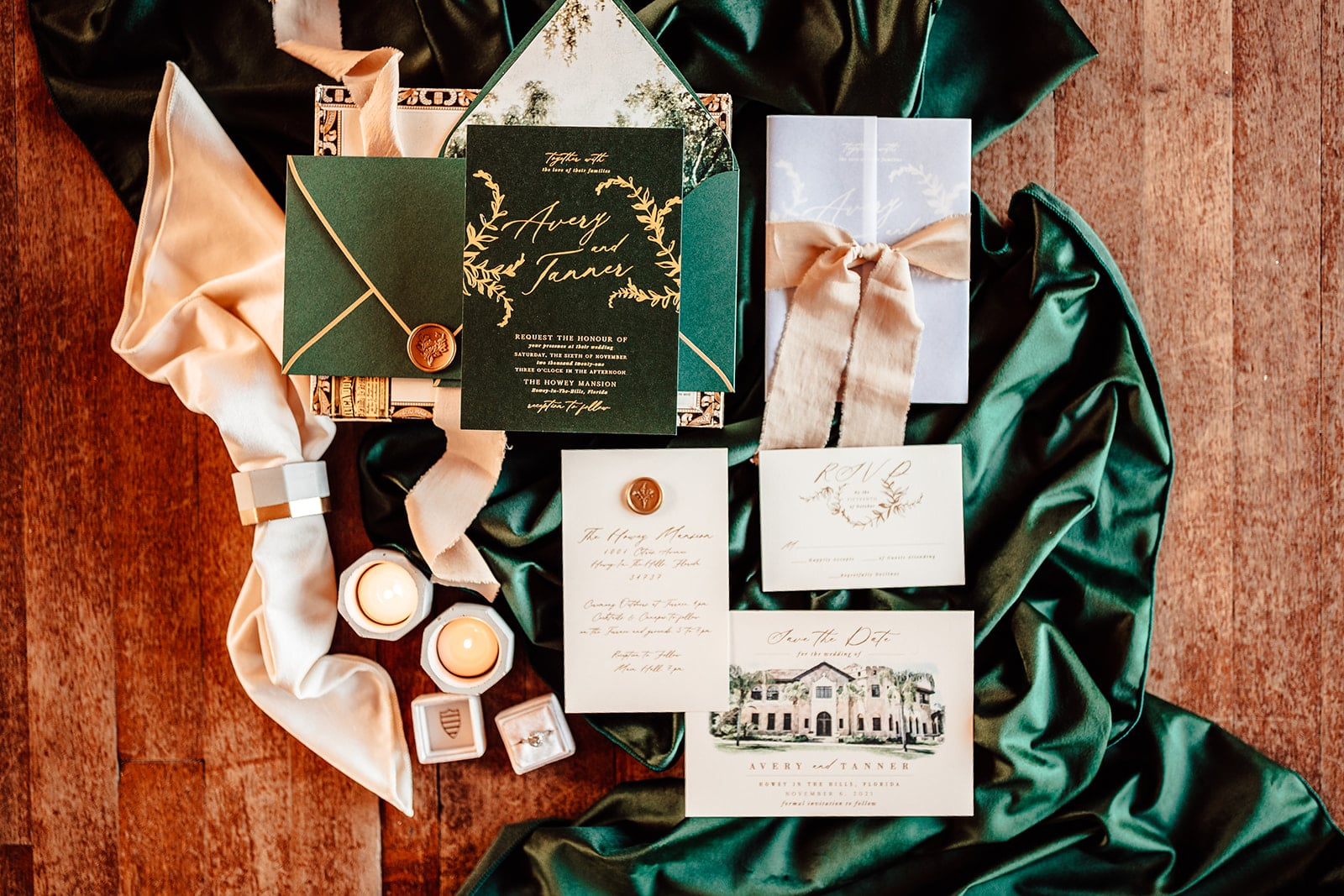 flat layout of elegant emerald green and gold wedding day invitation suite with emerald green linen underneath