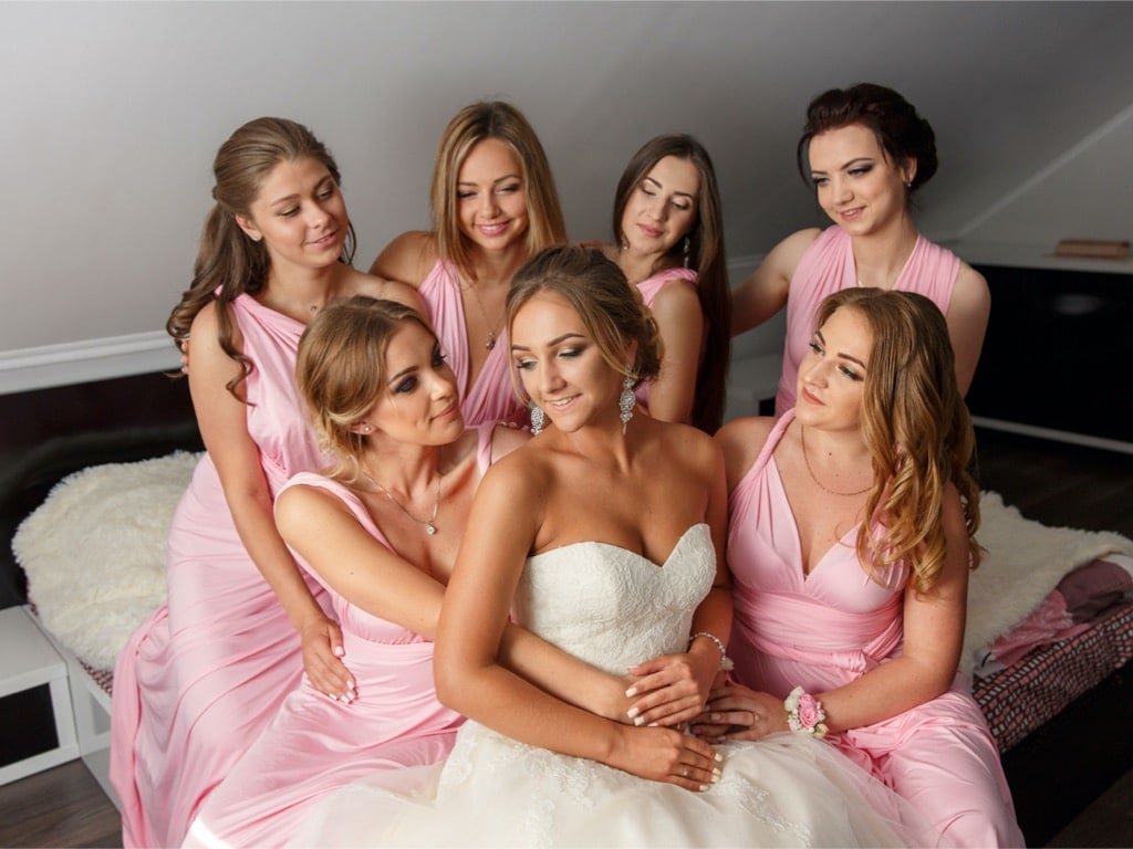 Ever After Beauty bride sitting with bridesmaids around her hugging