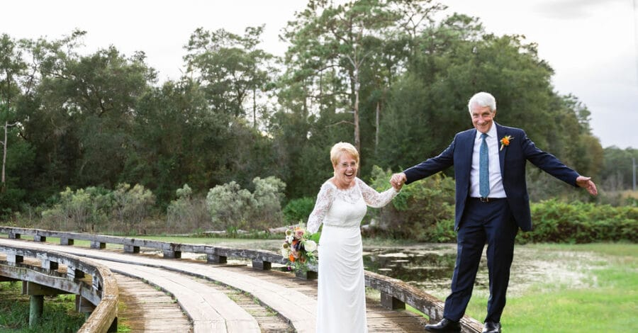 groom balances on the raised edge of wooden bridge smiling as bride holds his hand and bouquet