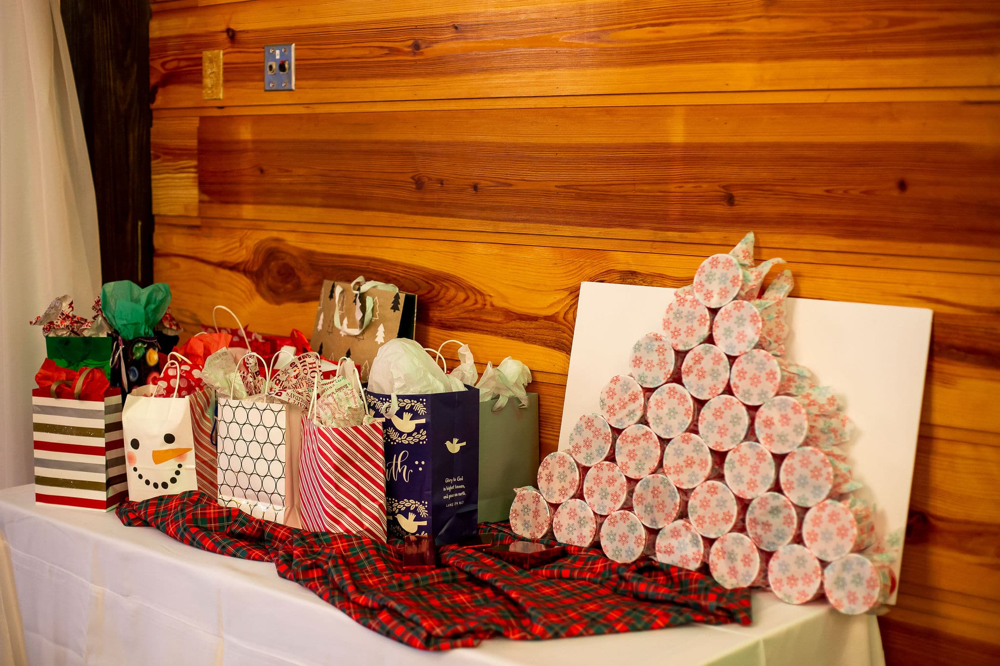 table in front of wooden wall with many christmas gift bags on top and a punch the hole game next to it on top of plaid linen