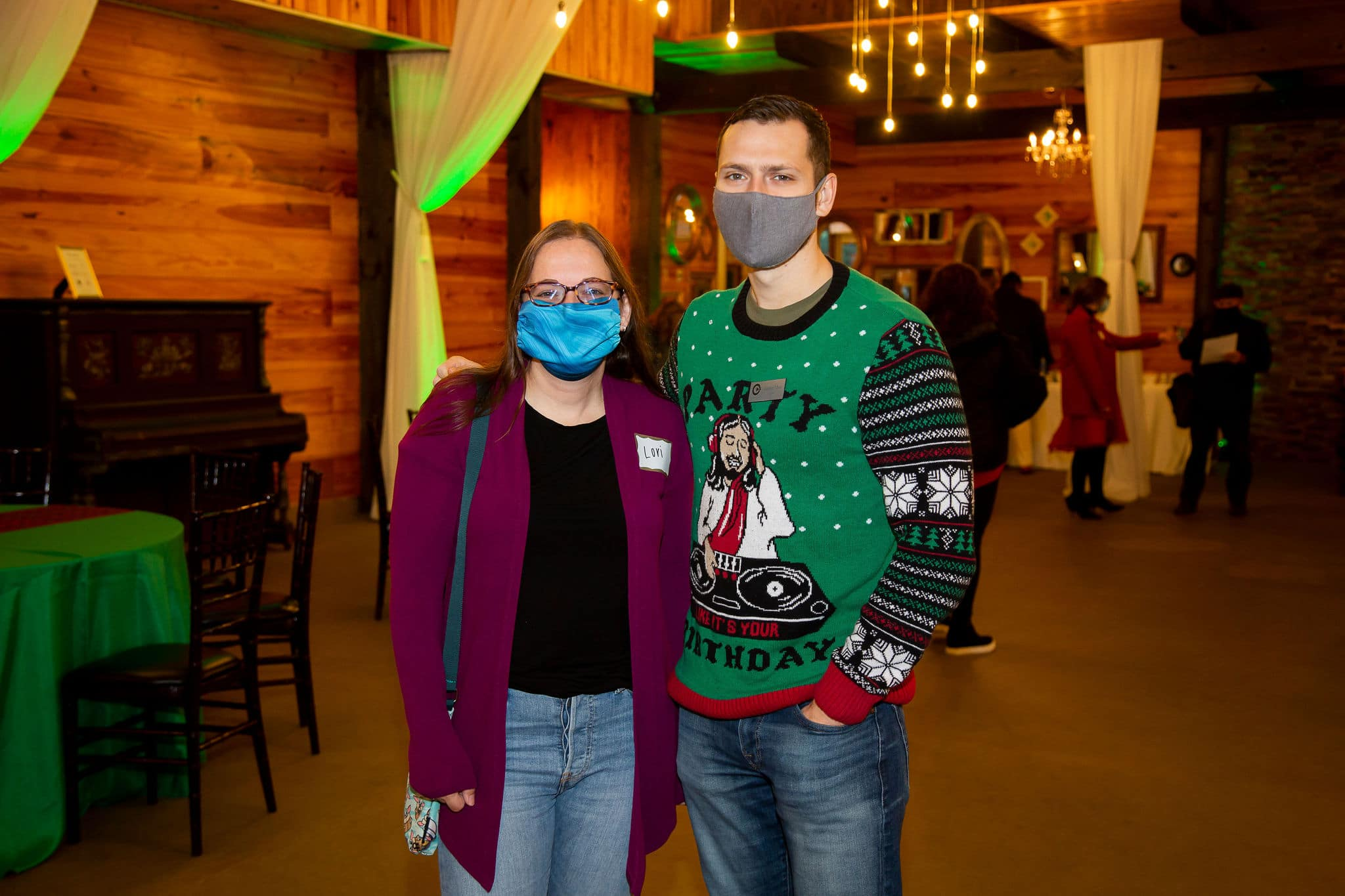 man wearing dj christmas sweater and grey mask stands next to woman wearing black shirt and purple coat with blue mask on