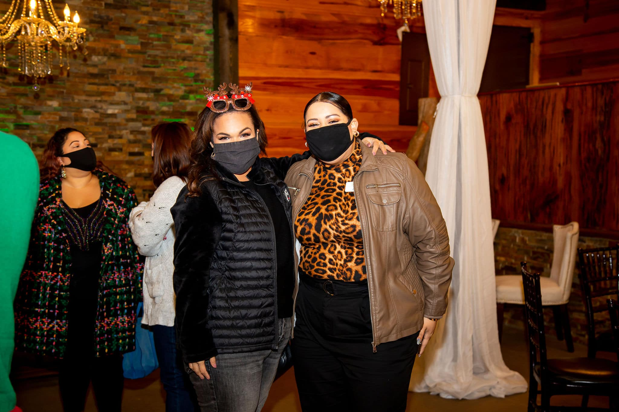 woman wearing black jacket and festive holiday sunglasses on head stands next to woman with leopard print shirt and brown jacket while at holiday party