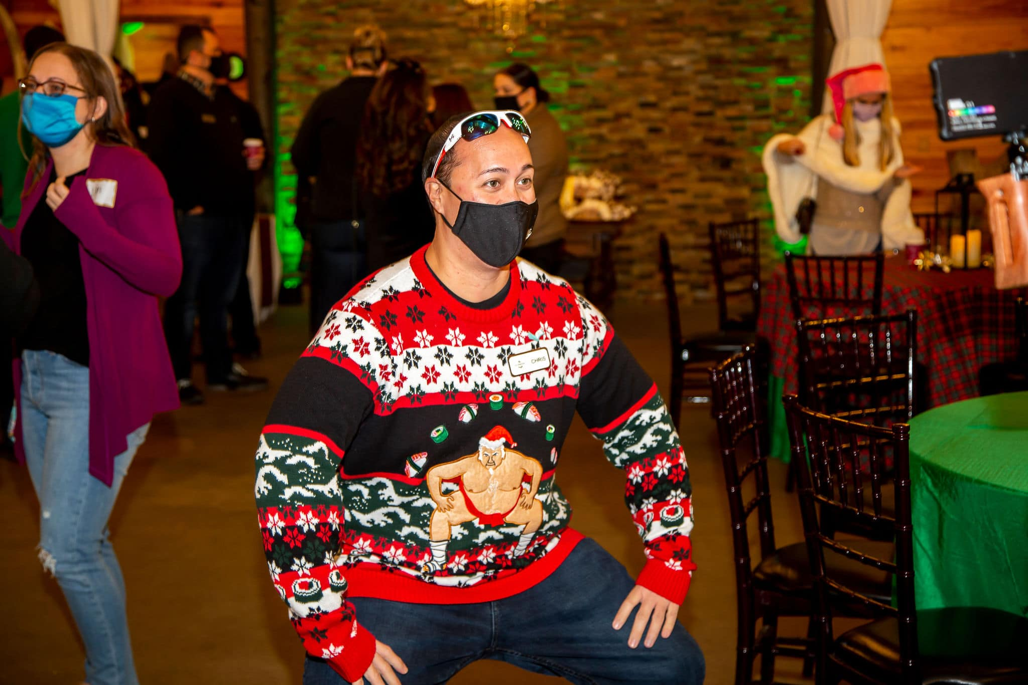 man wearing sumo wrestler festive sweater replicates pose of sumo wrestle on sweater with knees bent and hands on legs while wearing black face covering and sunglasses on head