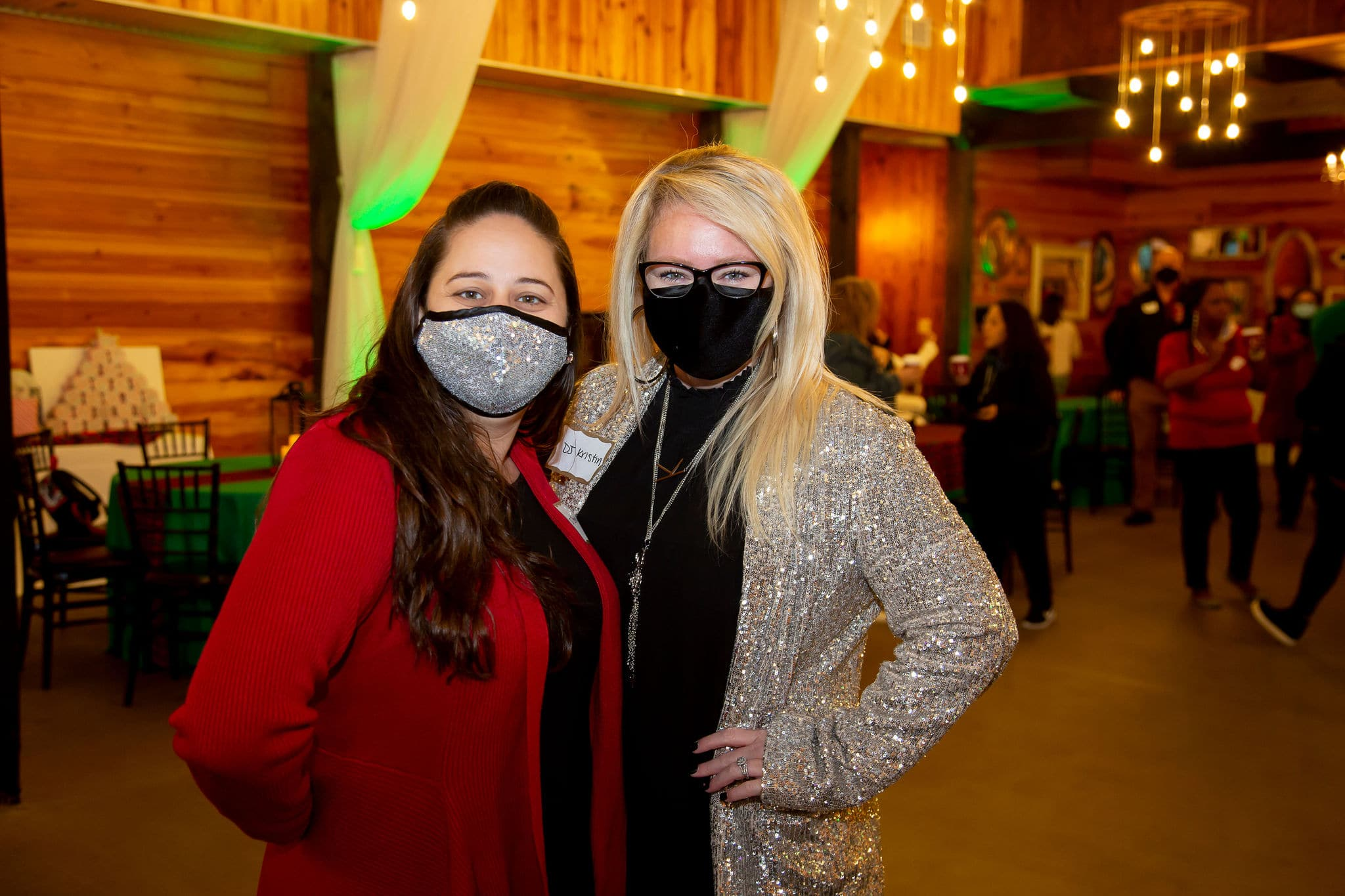 woman wearing silver glitter face covering and red sweater stands next to blonde woman wearing black shirt and gold glitter jacket with glasses and black face covering on