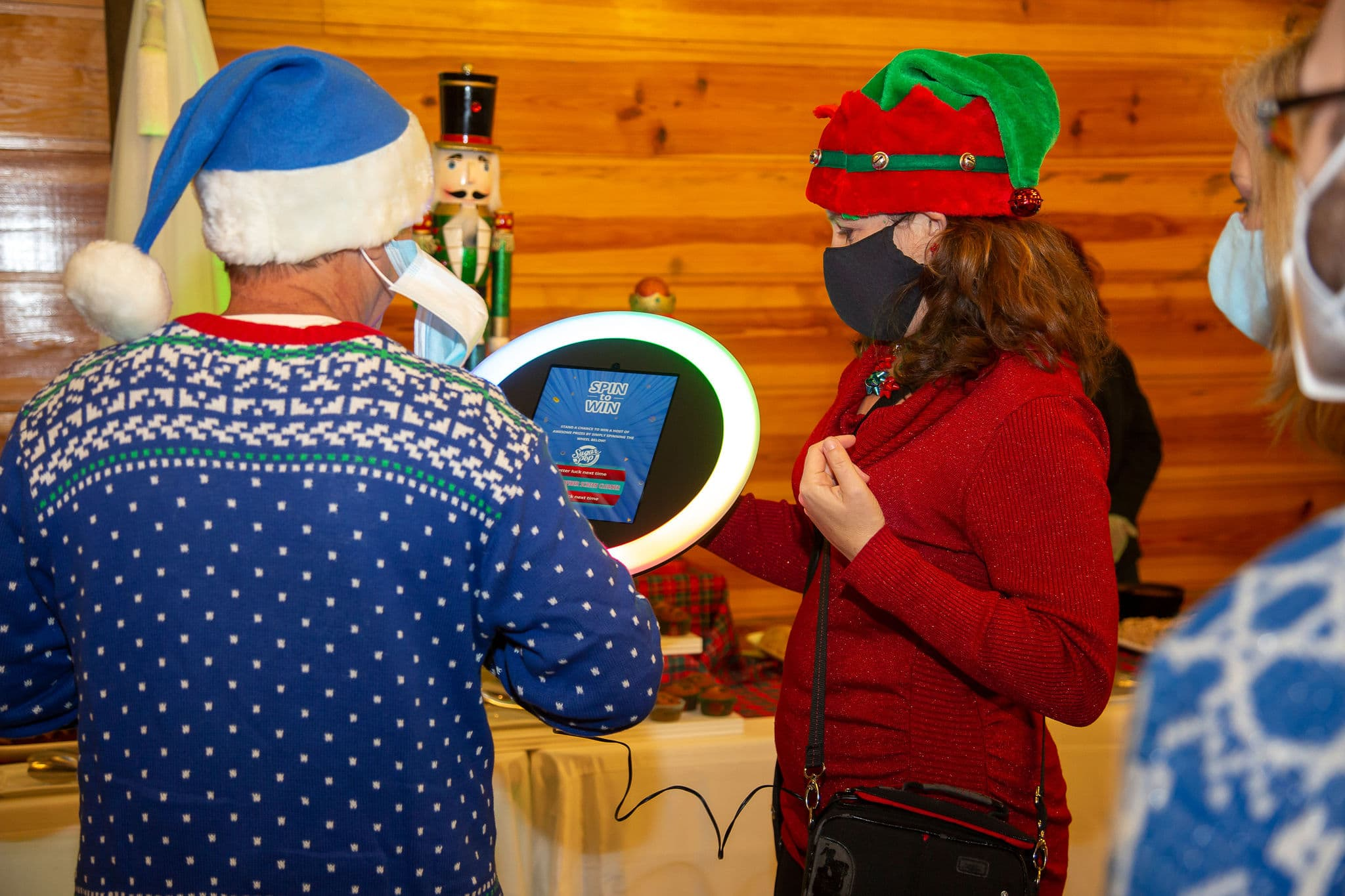 guest in festive blue santa hat and blue holiday sweater using roaming photobooth with the attendant holding the machine while wearing elf hat