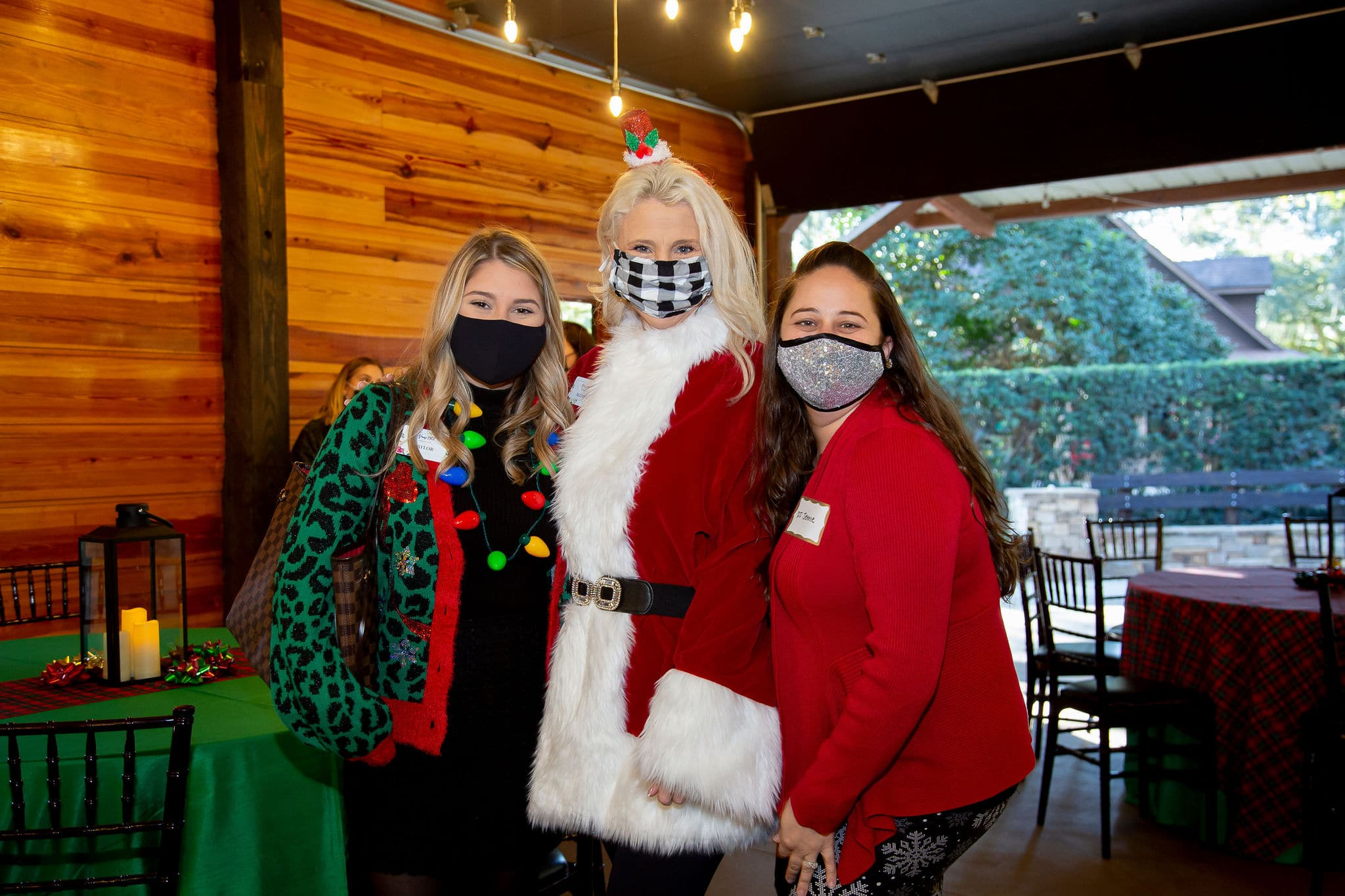 three woman stand together for a photo the one on the left wearing a green leopard print sweater with light up christmas lights necklace the woman in the middle wear big red and white santa jacket and the woman on the right wears a glitter face covering with a red sweater