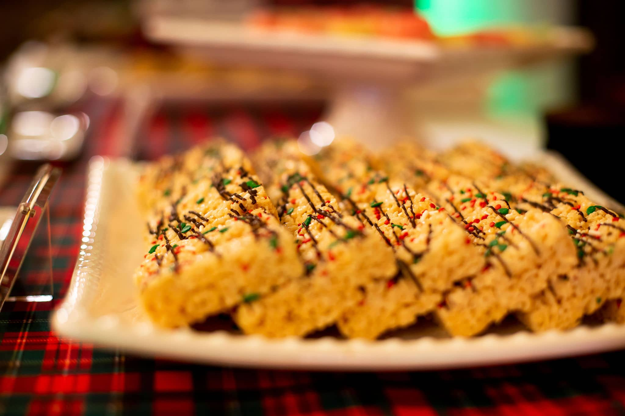 close up of rice krispie treats with chocolate drizzle and green white and red sprinkles on white plate sitting on top of plaid linen