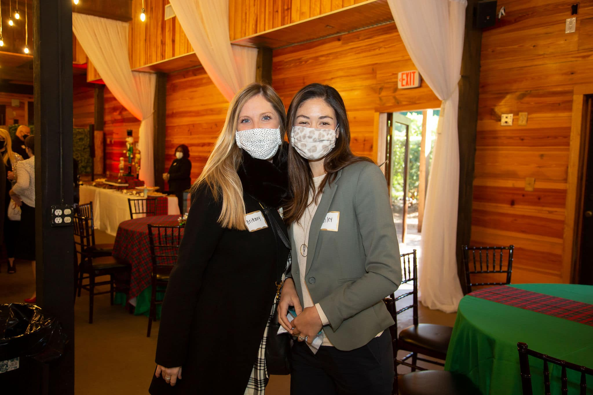 two woman stand together with light colored face coverings for a photograph wearing jackets and name tags next to table with festive green linen