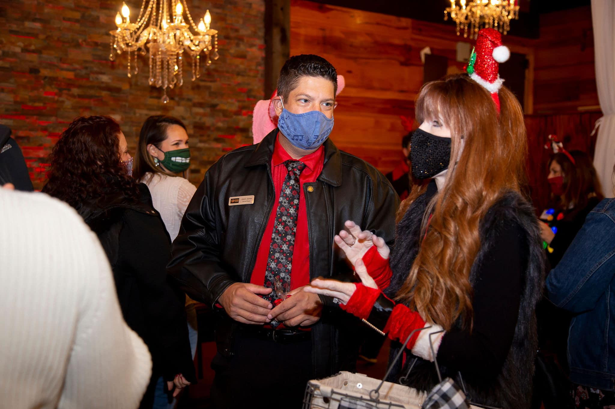 red haired woman wearing santa hat headband and santa-like gloves stands next to man wearing black jacket and red shirt with a holiday tie