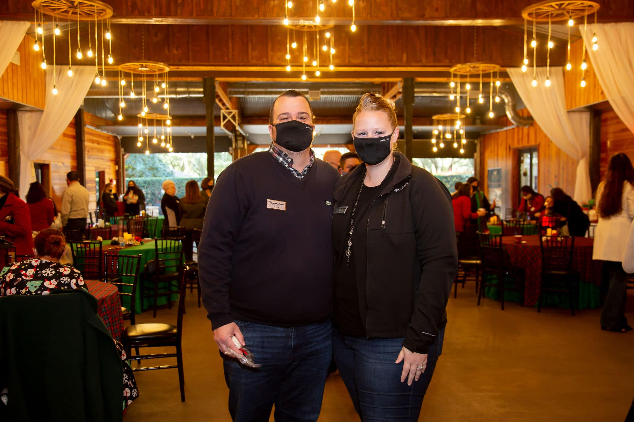 husband and wife stand together for photograph in the middle of holiday party wearing dark jeans and darker colored sweater and jacket both with branded black face coverings