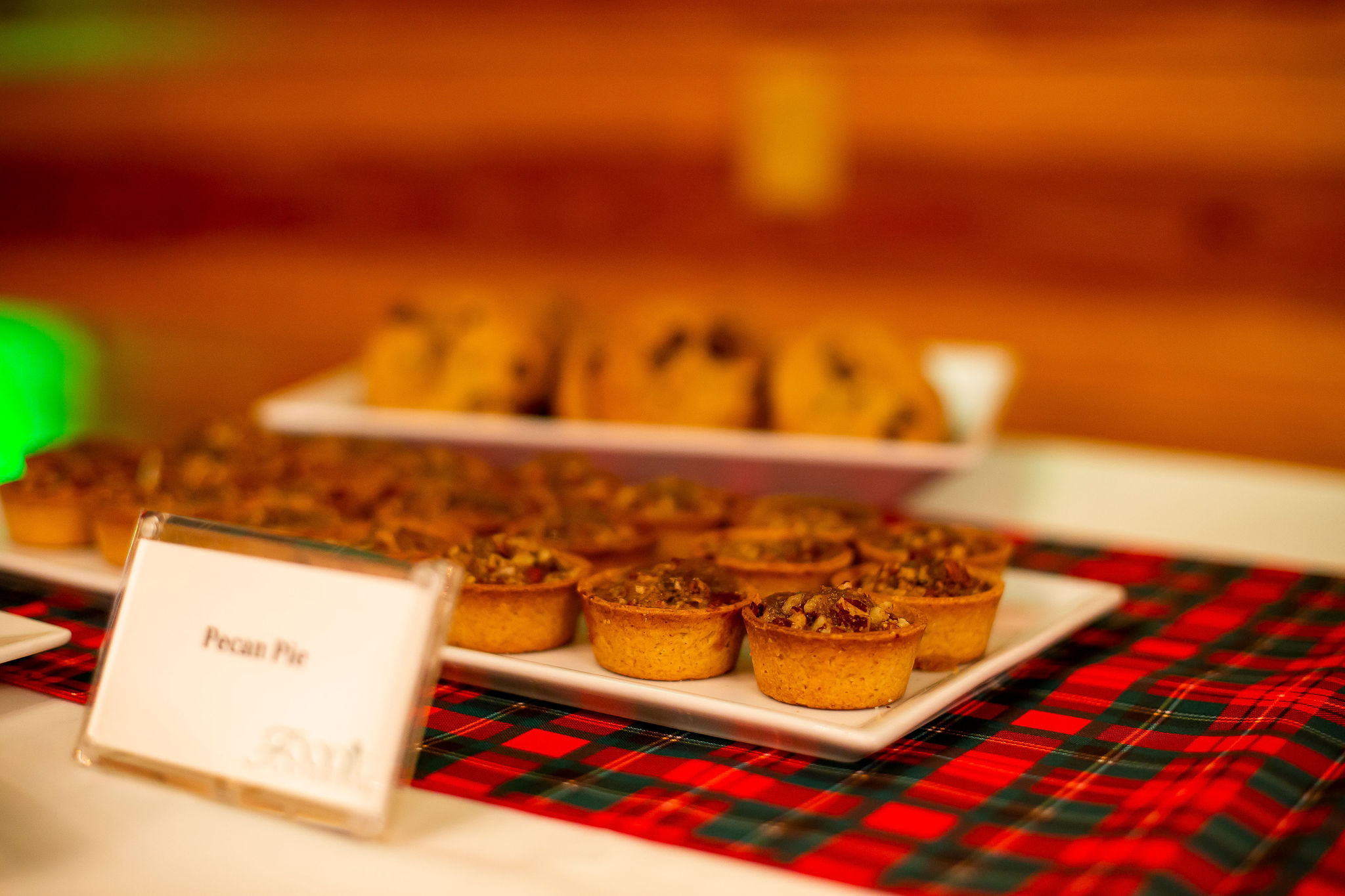 plate of mini pecan pies in front of plate of cookies on plaid green and red linen with sign for pecan pies in front