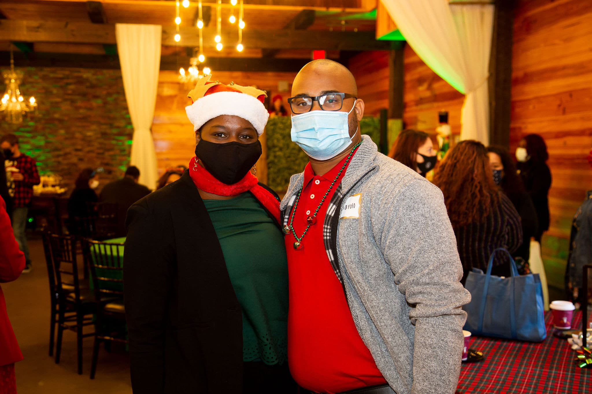 man wearing red polo and grey jacket stands next to woman wearing red scarf green shirt and black sweater both wearing face masks