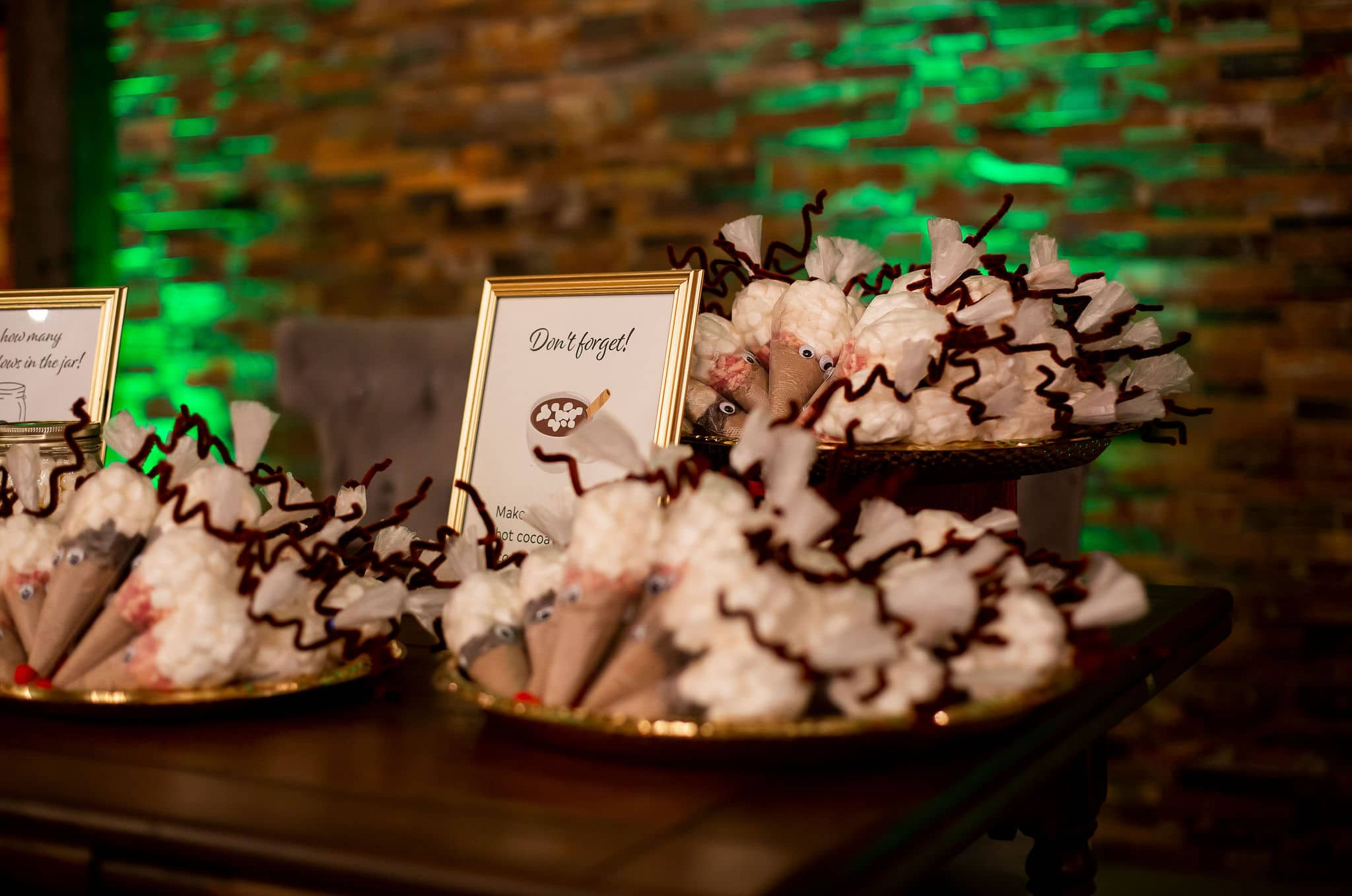 cones filled with hot cocoa powder and toppings of chocolate chips and candy canes on three different platters with sign next to it and green uplighting behind