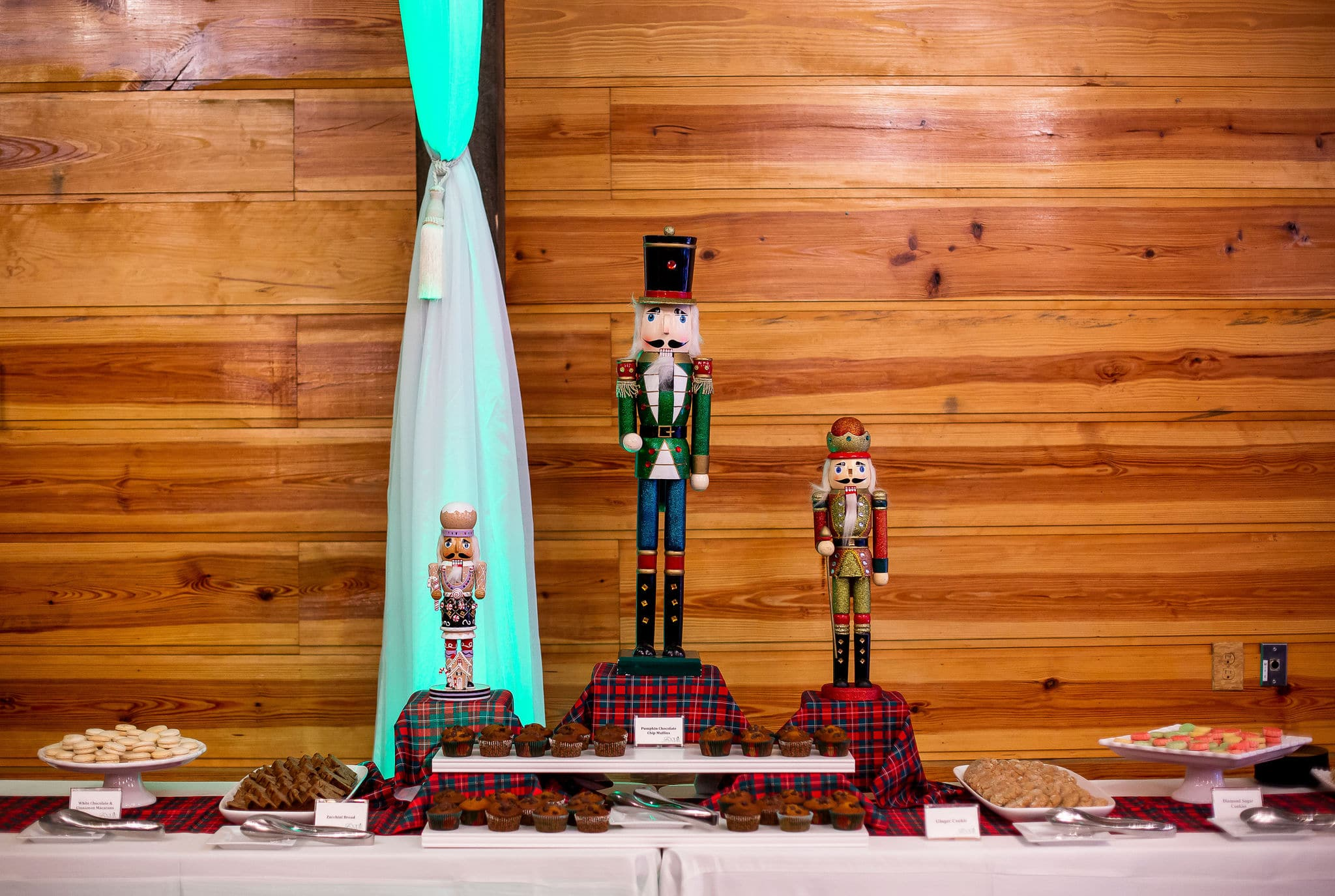 table in front of wooden wall with green and red plaid fabric with desserts displayed on top and three different size nutcracker figures