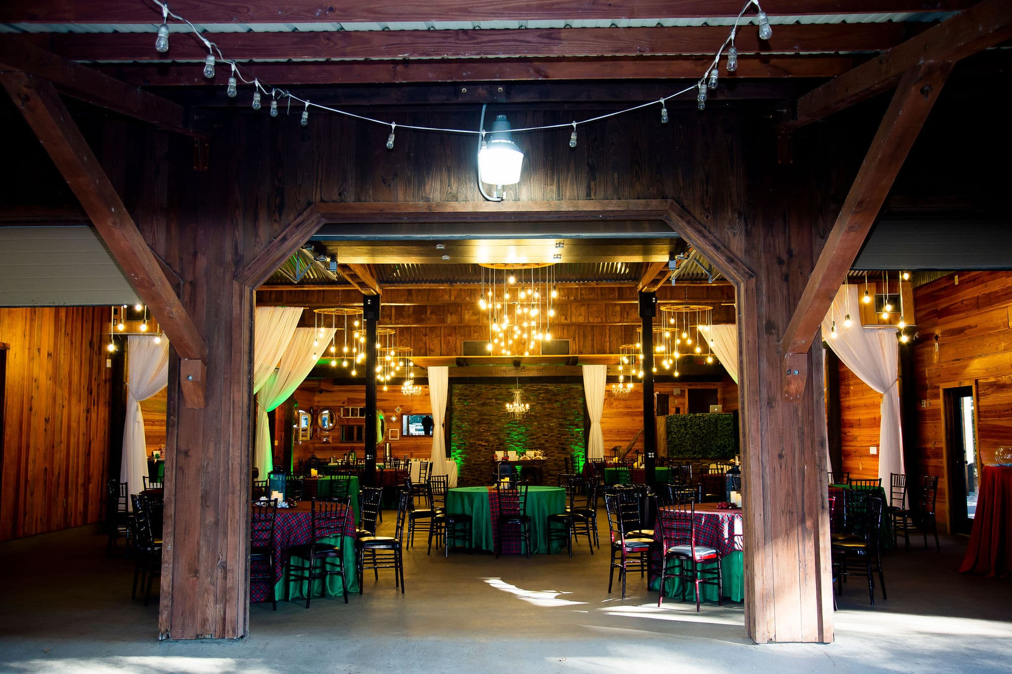 looking into wedding reception space from outside of garage doors with tables and chairs set up for holiday party