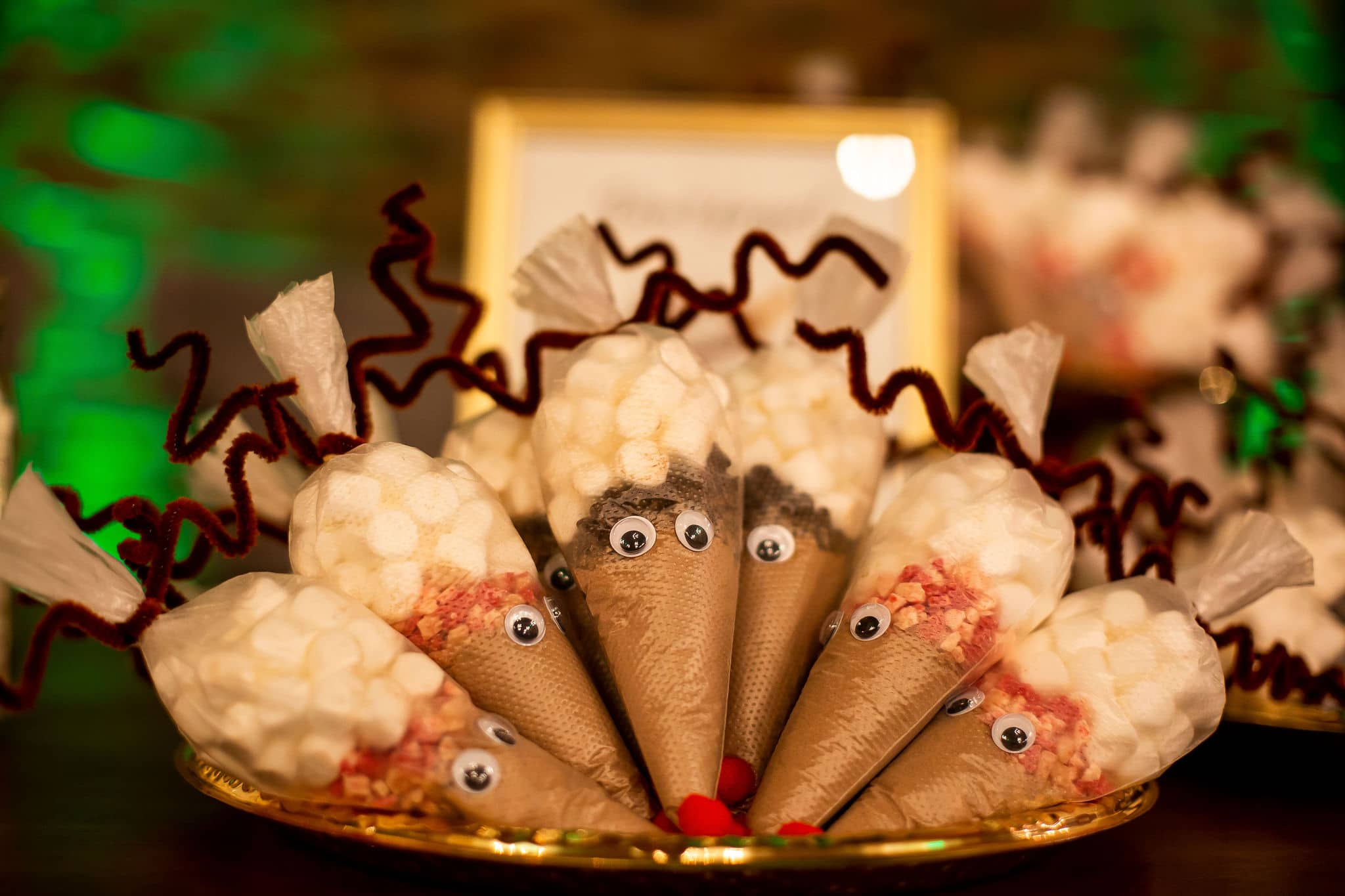 close up of decorated cones filled with hot cocoa mix and chocolate chips or candy canes with marshmallows and crafted into reindeers