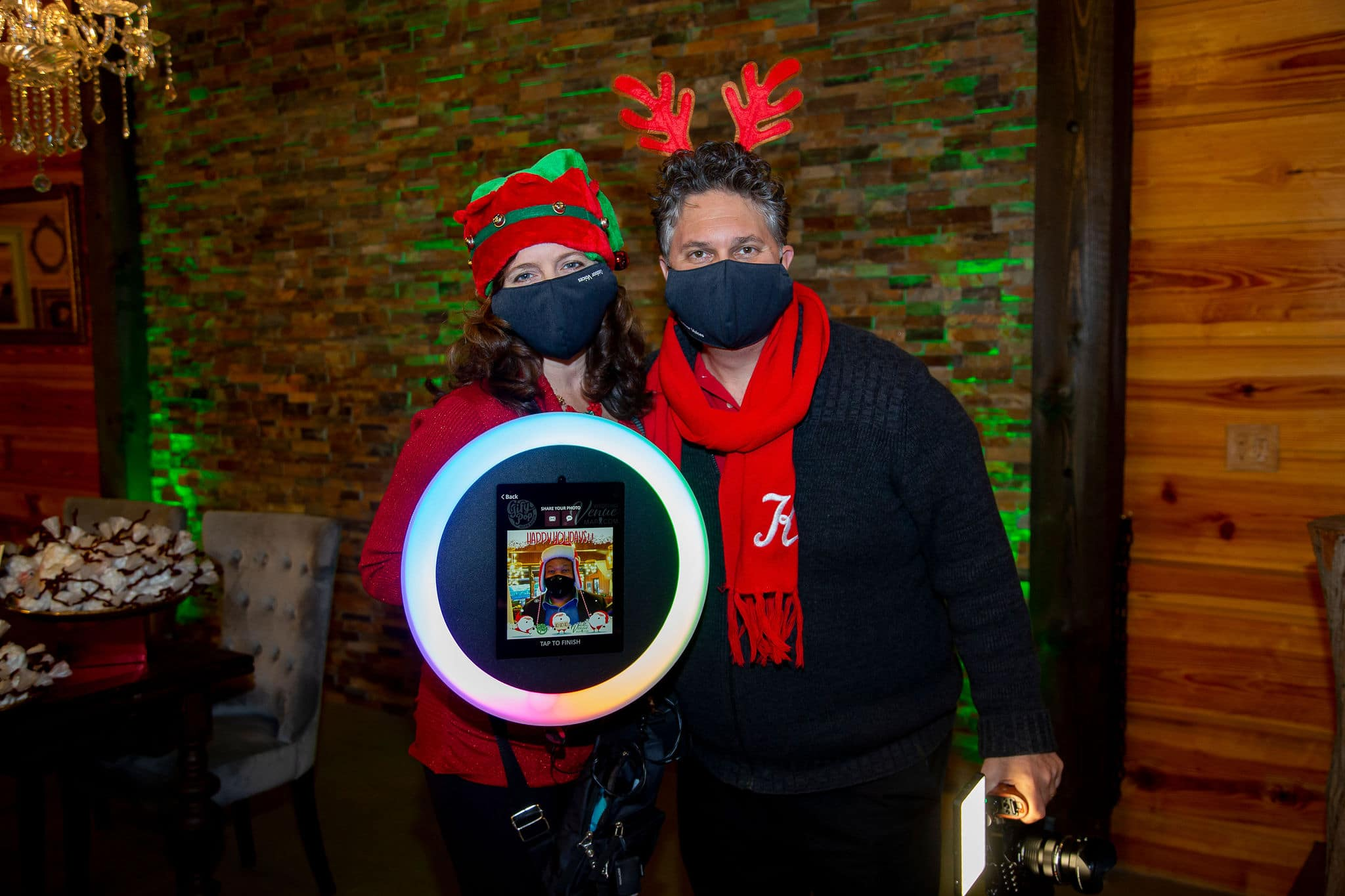 man and woman wearing festive hat and reindeer headband holding roaming photobooth machine and video camera