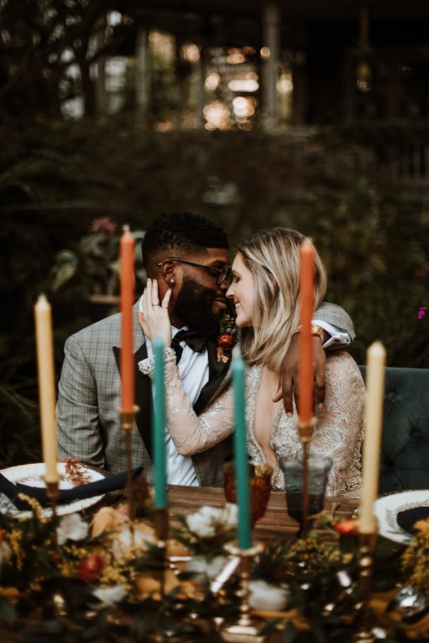 bride and groom sitting at table behind tall multi color candlesticks and eclectic table setting