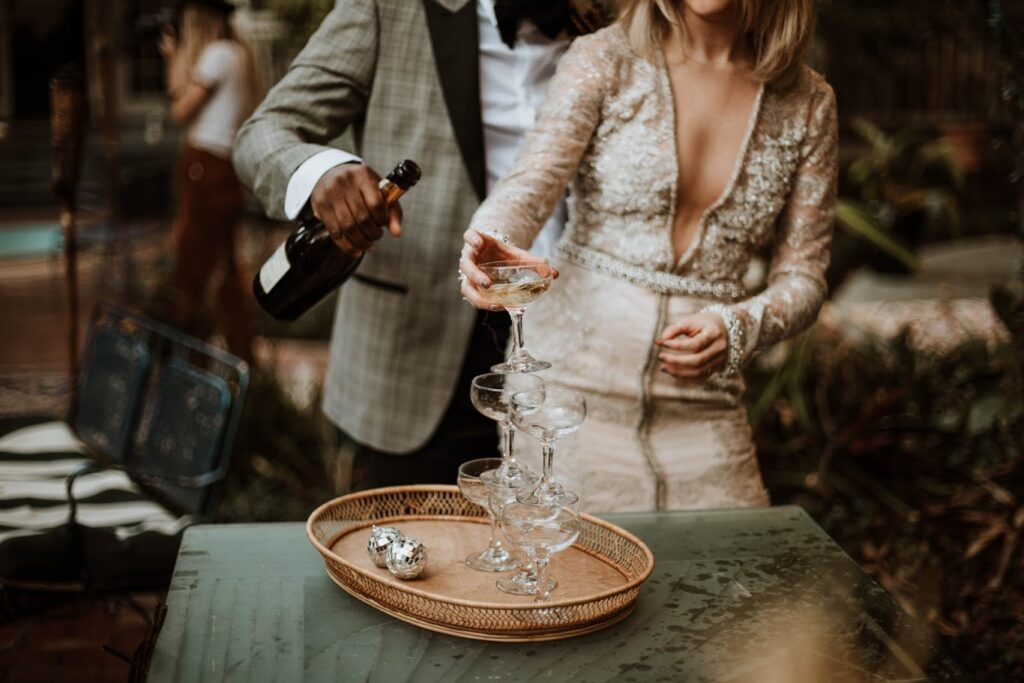 bride in lace dress and groom in gray tux pouring champagne into glasses on wood tray