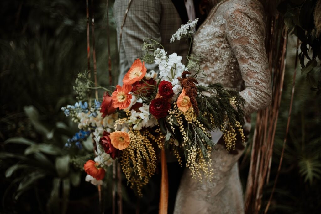 wedding bouquet with variety of flowers in red, orange and white with flowing greenery