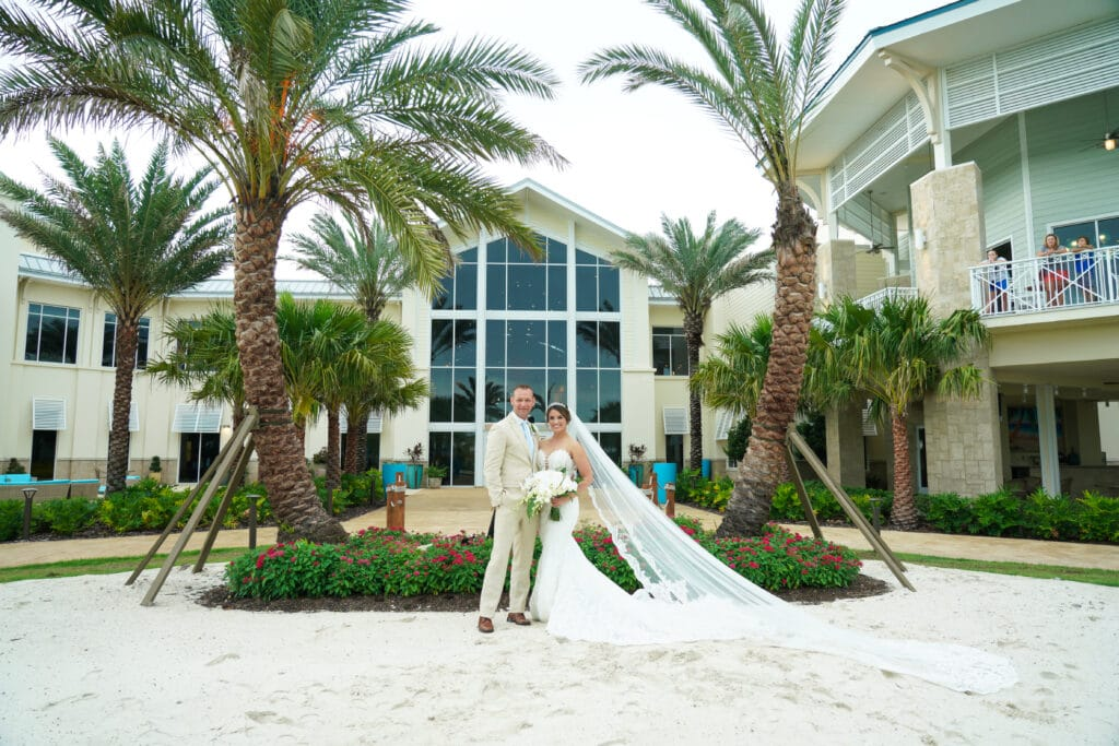bride and groom in sand in front of palm trees and windows - margaritaville resort orlando wedding venue