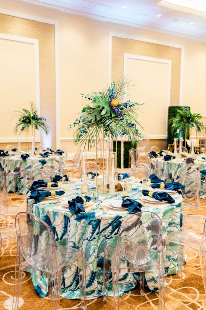 indoor reception with tropical table cloths, clear acrylic chairs, and bright floral arrangements - margaritaville resort orlando wedding venue