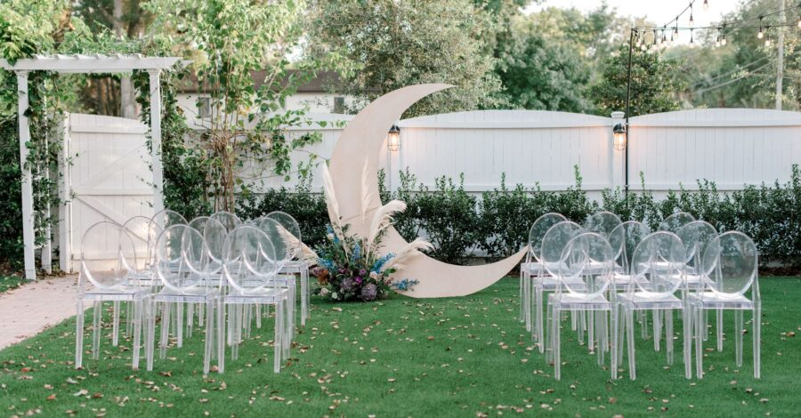 moon shaped arch on green lawn with clear chairs set up for wedding ceremony space in front of white fence