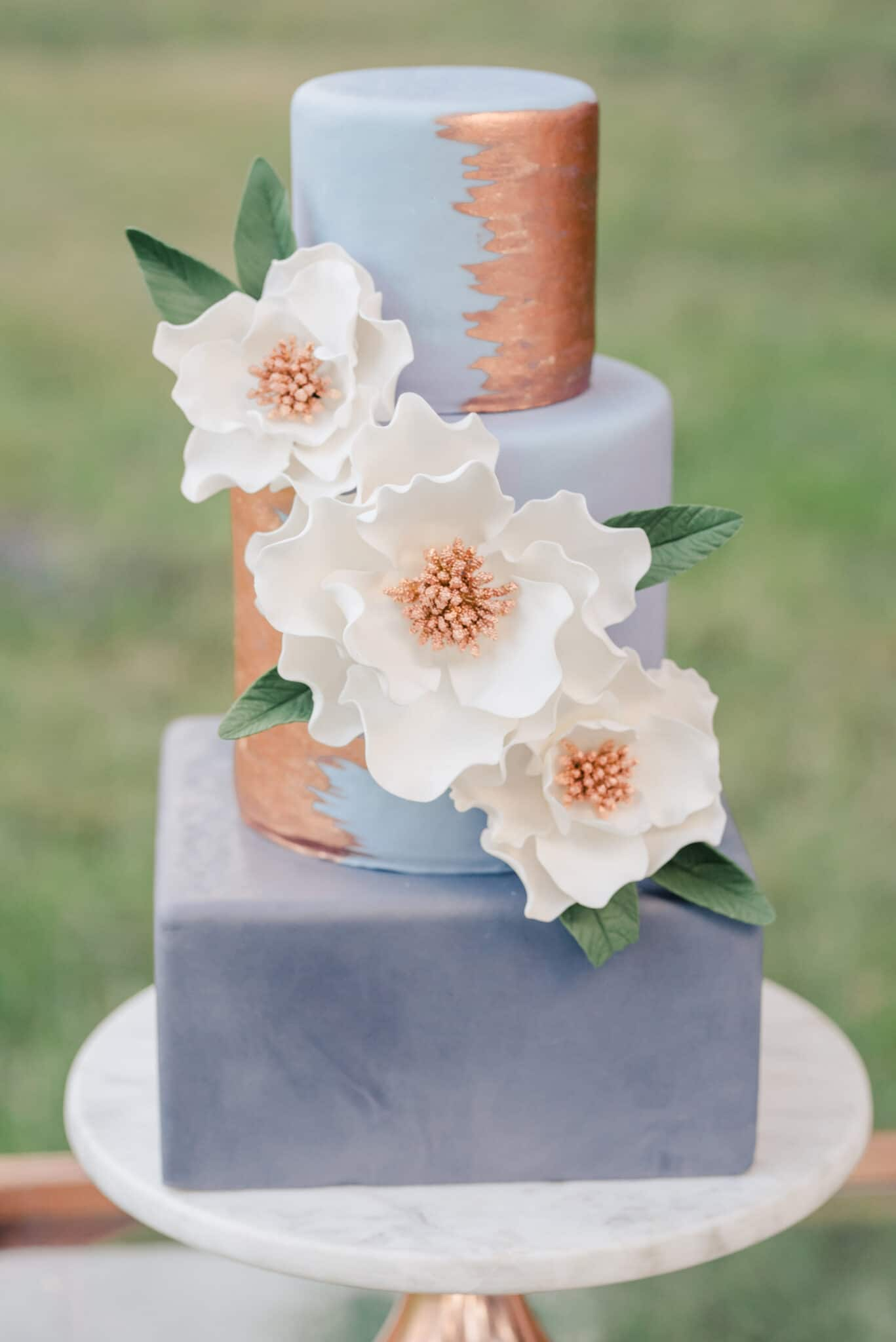 Blue cake with white flowers and gold with a square base