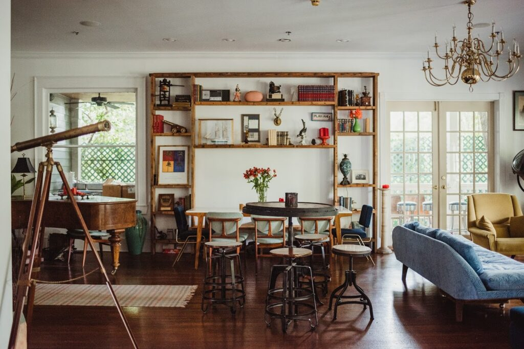 eclectic living space with wood floors, multi color furniture, bookshelf and telescope