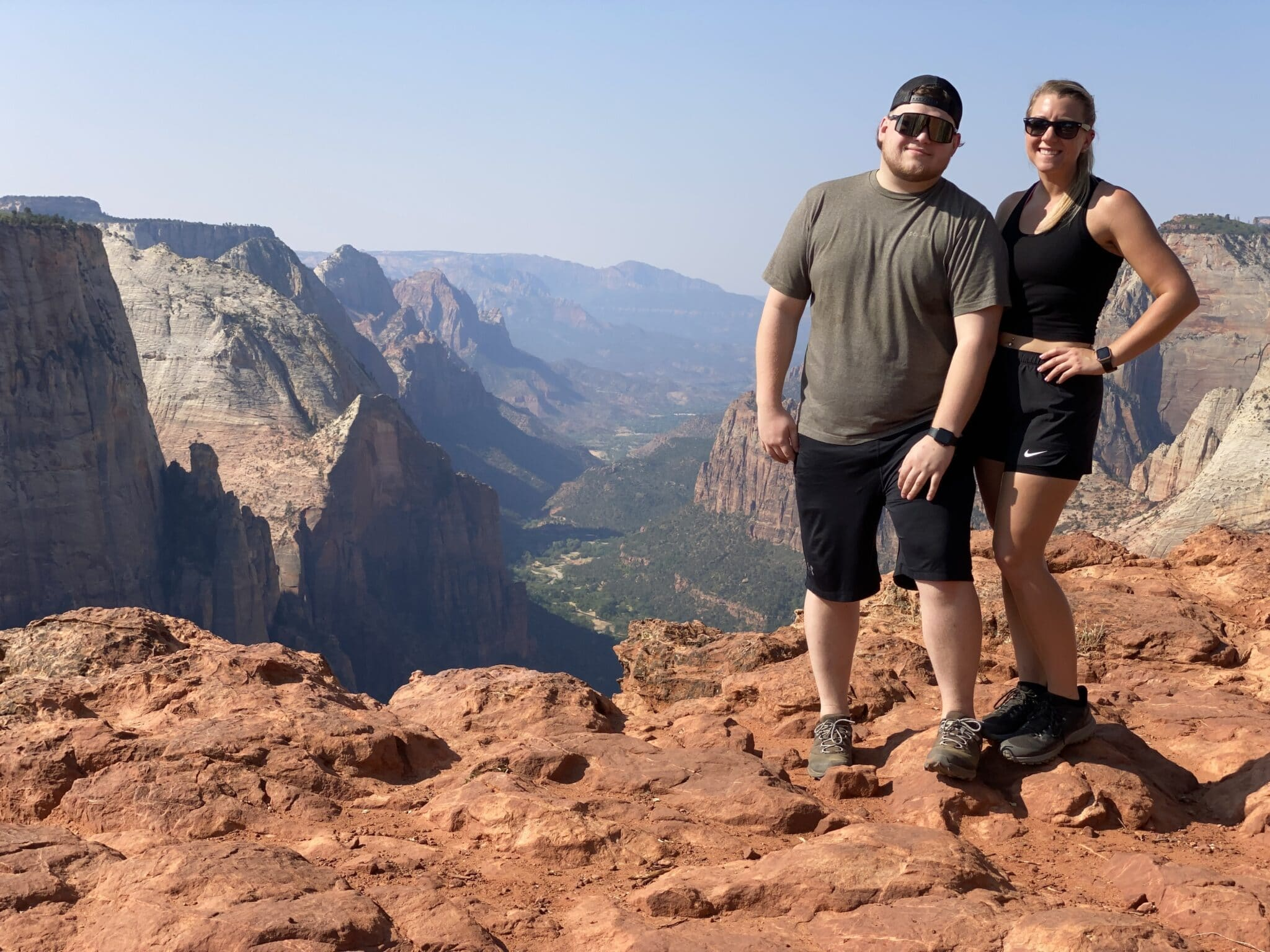 couple wearing athletic clothes stand on the edge of mountain top overlooking view of national park both with sunglasses on