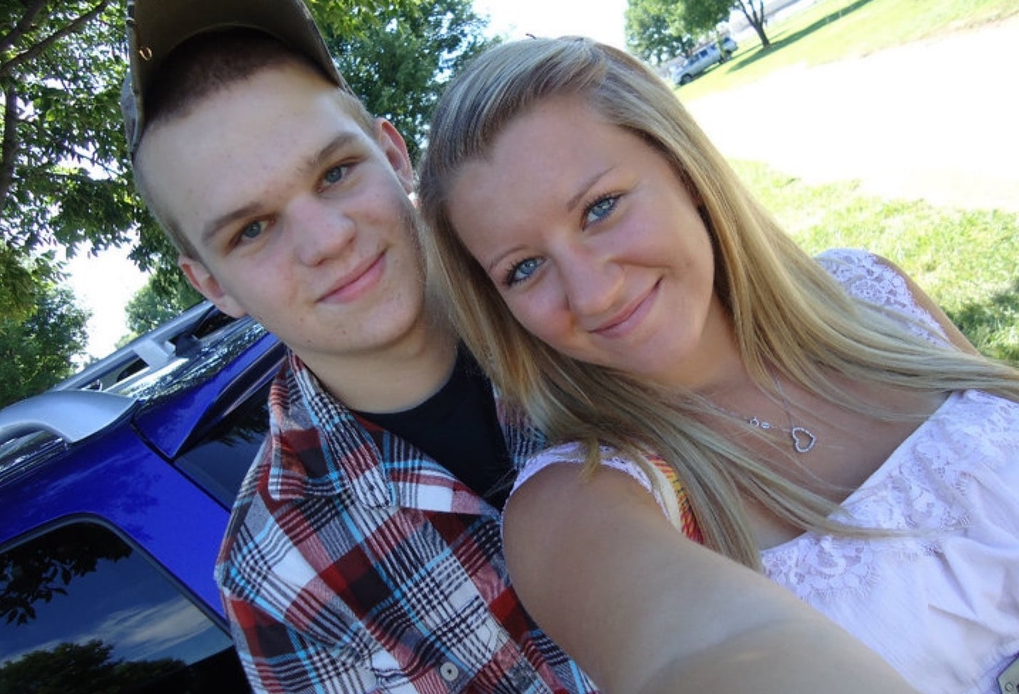 young couple taking a selfie the man wearing a hat and plaid shirt the girl with blonde hair wearing a light pink sleeveless shirt